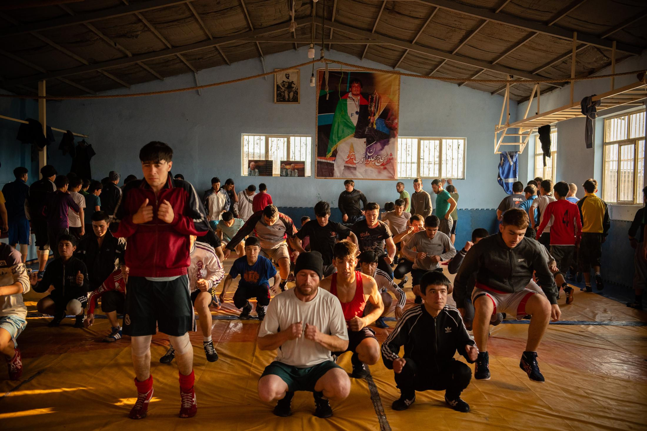 KABUL | AFGHANISTAN | 2/6/19 | Members of Maiwand Wrestling Club warm up with repetitions under the instruction of their coach before they start practicing their wrestling techniques with their partners. On Sept. 5, an Islamic State suicide bomber looking for Shiites to kill, burst in and took the lives of as many as 30 people at the club. Despite the attack, everyday, over 100 members, as young as 9 year old, come together to practice inside Maiwand Club. Kiana Hayeri for The New York Times
