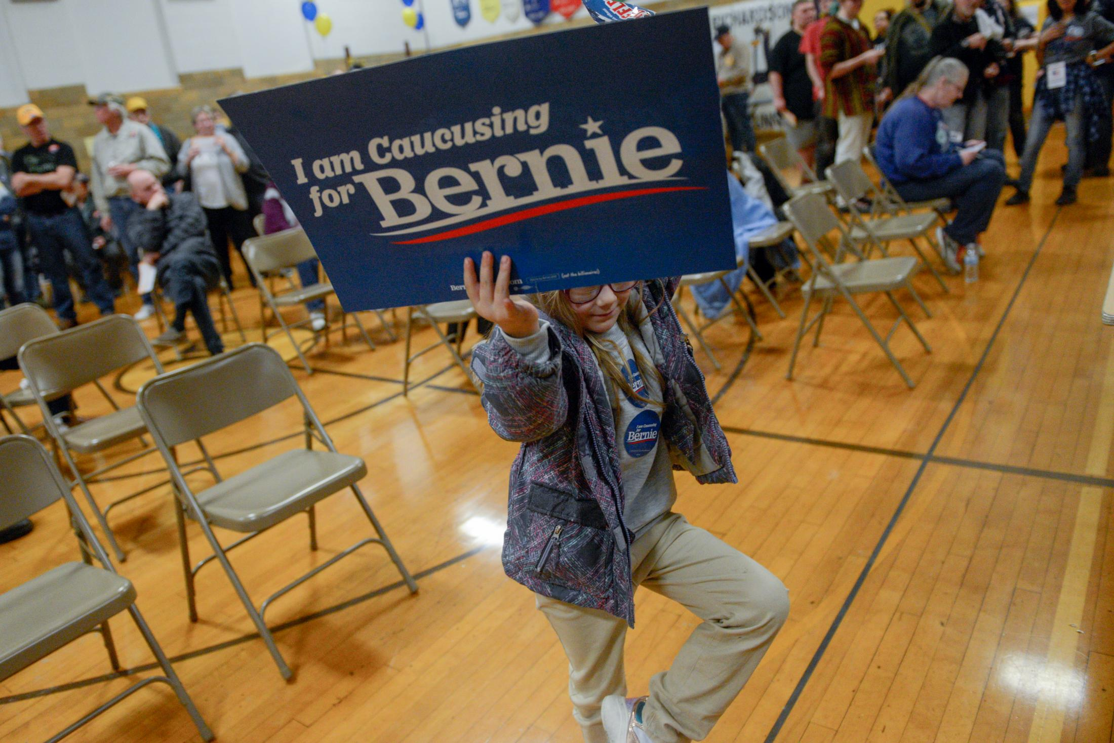 A child holding a Bernie Sanders campaign sign dances by the observer table at Richardson Elementary School for the Fifth Precinct caucus on Monday, February 3, 2020, in Fort Madison, Iowa. The Sanders campaign received four delegates from the district.
