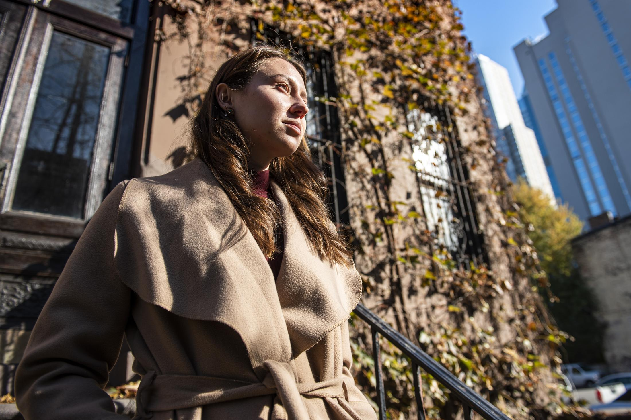 Madison Kozco, 25, sewing technician at Parsons School of Design, stands on a nearby stair of her apartment in Manhattan, New York, NY, on Friday, Nov. 15, 2019. She was a former student at PAFA who reported her rape to campus authorities in early 2016.