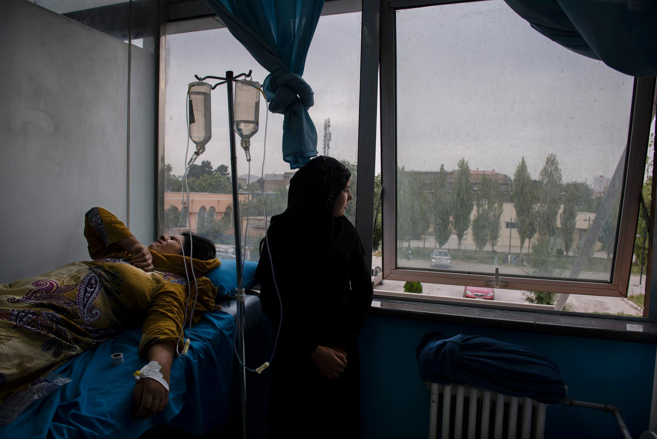 KABUL, AFGHANISTAN | 2017-07-15: 11 year old ???? care for her mother inside the oncology OPD of Jumhuriat Hospital while she receives her first dose of chemo treatment. 38-year-old Fatema was married off at age of 12 to a man 23 years older, Fatema's body have been through 21 pregnancy, with only 12 of the babies surviving. Married to an addicted man and struggling with extreme poverty, she had to give up two of her children at the time of birth and marry off her daughters at young age. Her 11 year old daughter (pictured here) was engaged when she was only 10. When Fatema was diagnosed with breast cancer, it took her 7 months to gather the money needed for her surgery and while she was supposed to be back 20 days later for her first chemo session, she was only able to borrow money for her chemo, a little over 3500 afs ($57), a month and a half later.