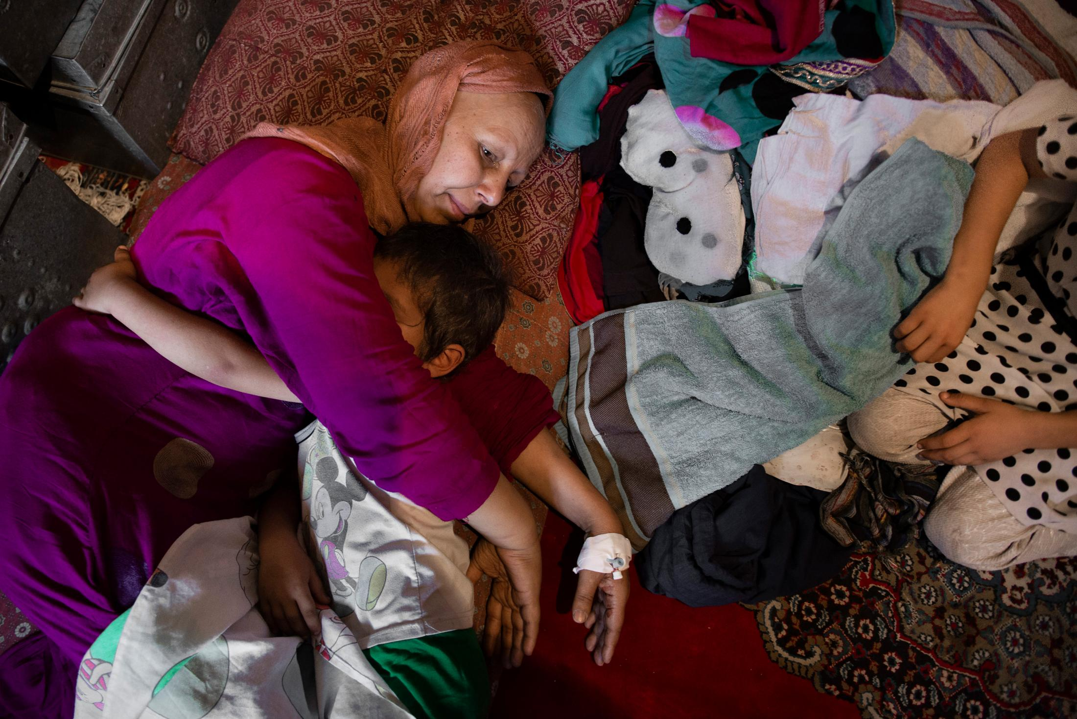 KABUL, AFGHANISTAN | 2017-07-17 | Parwin (44), feeling weak after receiving her 7th chemo treatment, lay down to rest in their small two room house in the neighbourhood of Fazel Beig. Her youngest son, Milad (4), noticing her mom is not feeling well lays down next her, hugging her tight.Darwin, herself, finished the 12 years of high school in 6 years, by studying on her own and taking exams. At age of 16, she entered the med school. When she was 19, after finishing her third year of university, she married her husband who is illiterate, and forced her to abandon her studies. She stayed home and raised her 8 kids, 2 of which have died from sickness. Despite her husband not liking his daughters going to school, Parwin fought for every one of them. Her oldest daughter, Fatema (17) just graduated from high school and wants to go to university to become a midwife. Her youngest daughter, just being 8, is in grade 5. Parwin and Fatema's greatest fear is that if she doesn't survive the cancer, the father will marry off the older daughters and stop them from going to school.