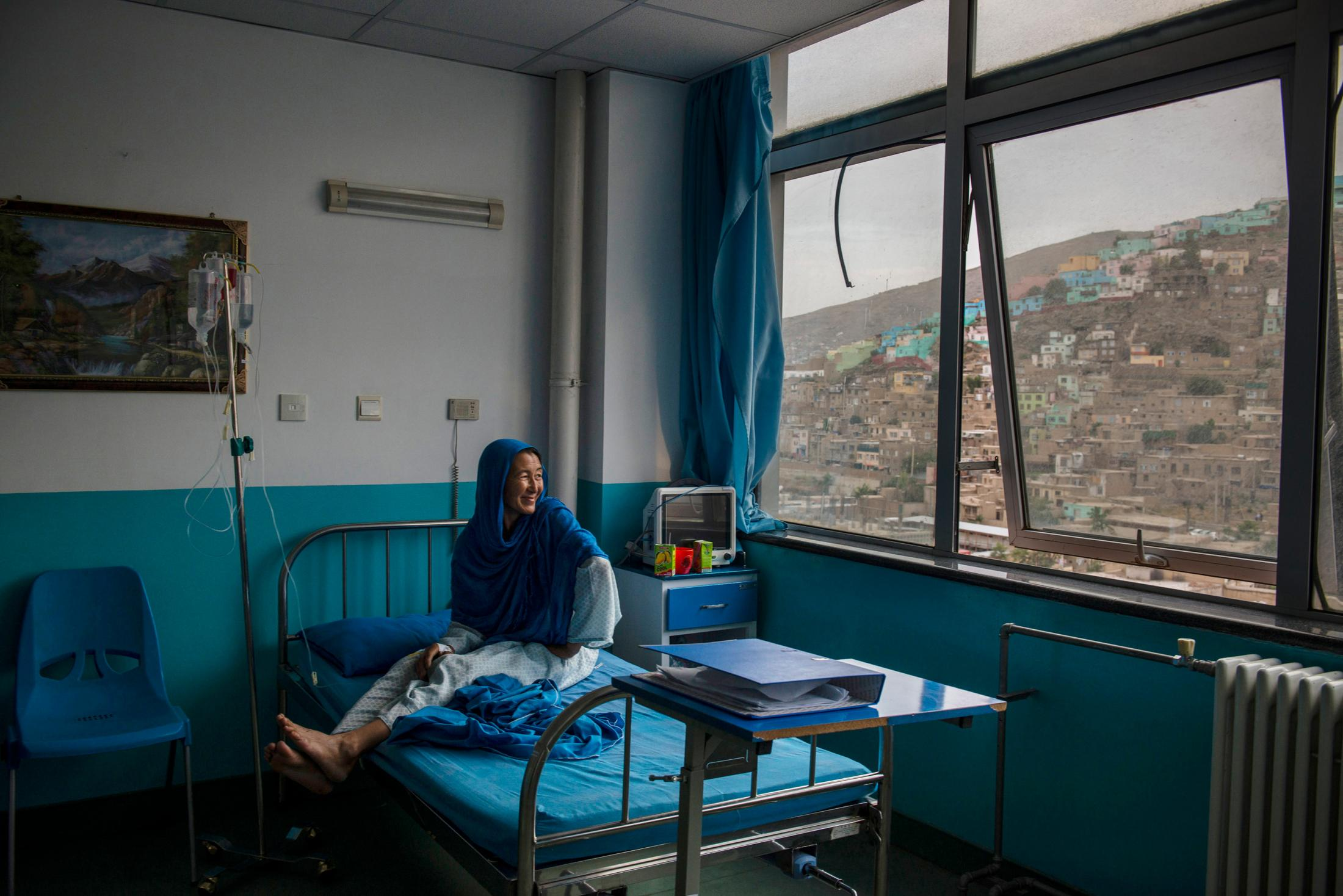 KABUL, AFGHANISTAN | 2017-07-15: Jamila (41) is prepared by the doctors and nurses for her first chemo treatment. Jamila and her husband travelled all the way from their village in Kunduz to Kabul, after the growing tutor in her left breast spread to her armpit and the pain became unbearable. In Kabul she was diagnosed with breast cancer stage four that has metastasis. She doesn't have long to live and she knows that. While holding on to a smile that once in a while disappears out of pain, talks about her rare marriage, a marriage out of love, with the man who is 6 years younger than her. Before leaving her village and knowing that she has probably reached the end, Jamila found her husband, whom she's still in love with, a wife. Someone who will continue to love and care for him and will be a mother to her 2 children.