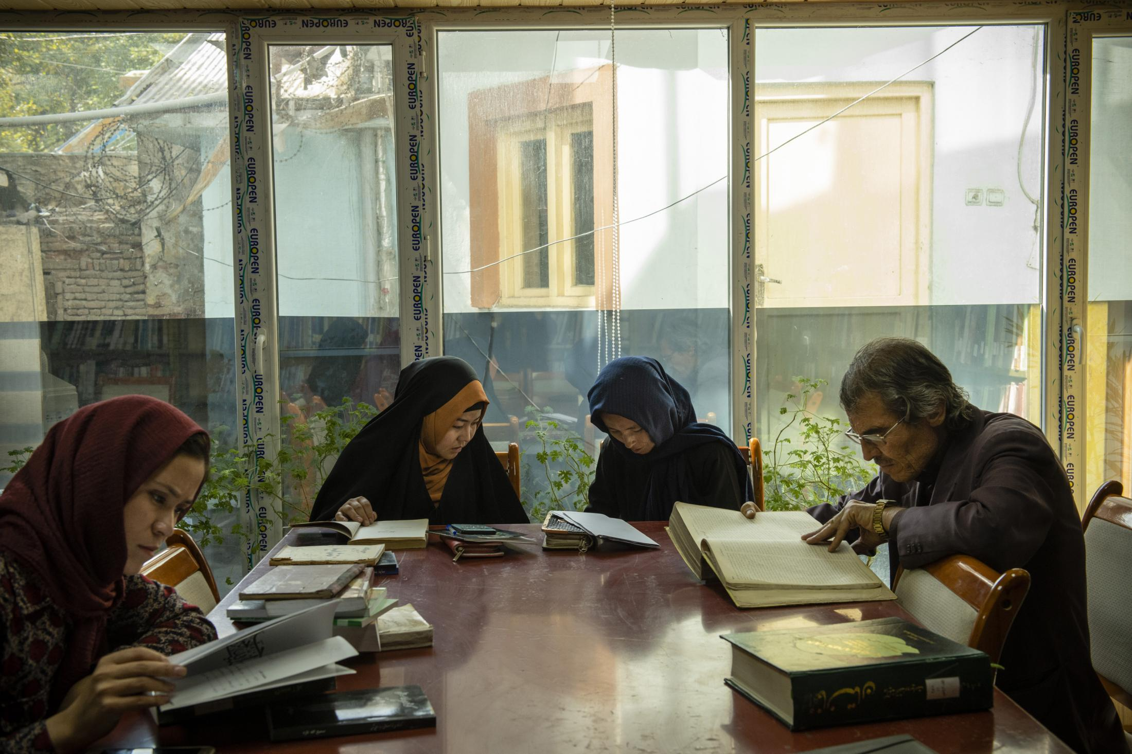 KABUL     10/16/19   Two university students whose thesis project is on the life and poetry of Haidari Wojoodi look trough the available books on the first floor of the public library, before they pay a visit to him at the newspaper archive department.