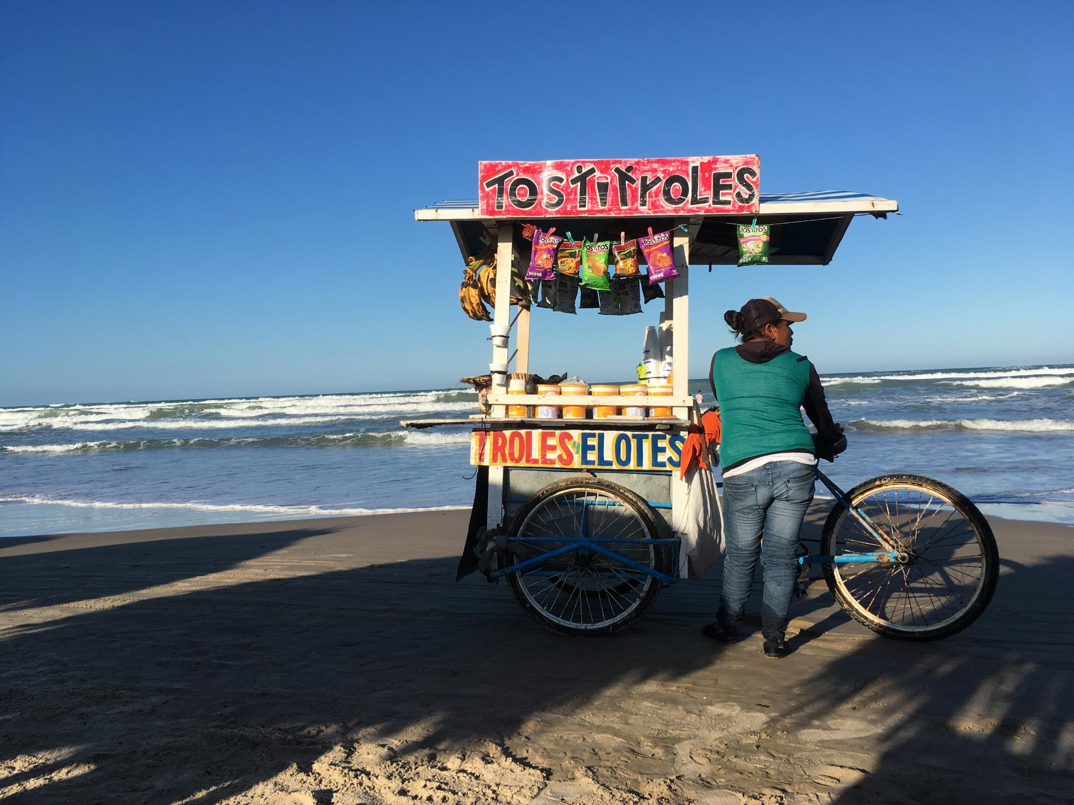 Playa Miramar, Tamaulipas, México. 2017. A lady waits for hungry customers to sell snacks to at the beach. I was there to hang out with friends while we chatted about our lives and listened to the popular reggaetón songs of that moment in time. Reggaetón: is a style of music which originated in Puerto Rico during the late 1990s. It is very popular in Latin American countries including México.