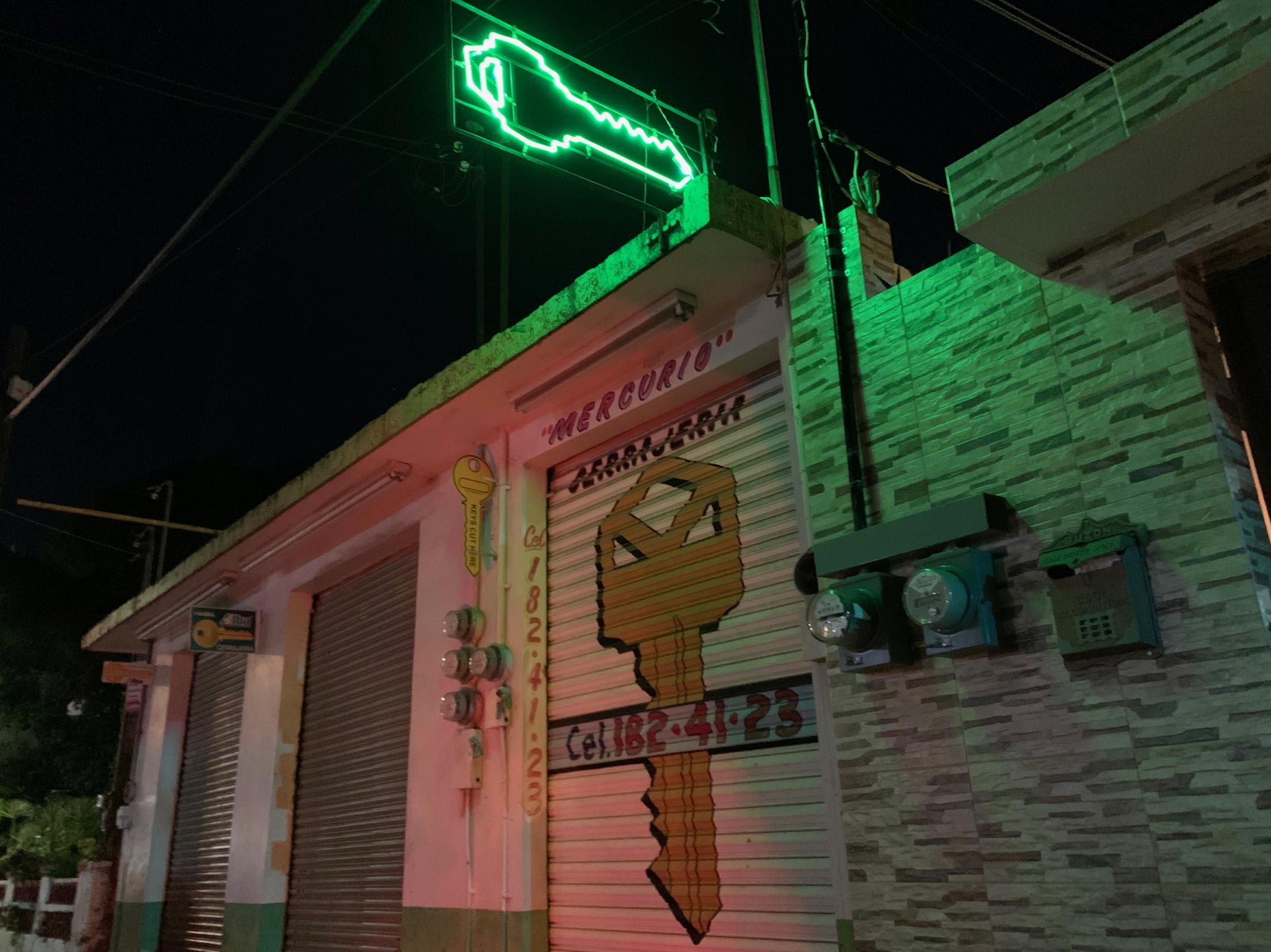 Tampico, Tamaulipas México. 2019. A locksmith business closed at night with bright neon sign in the shape of a key. I was on my home from a restaurant.