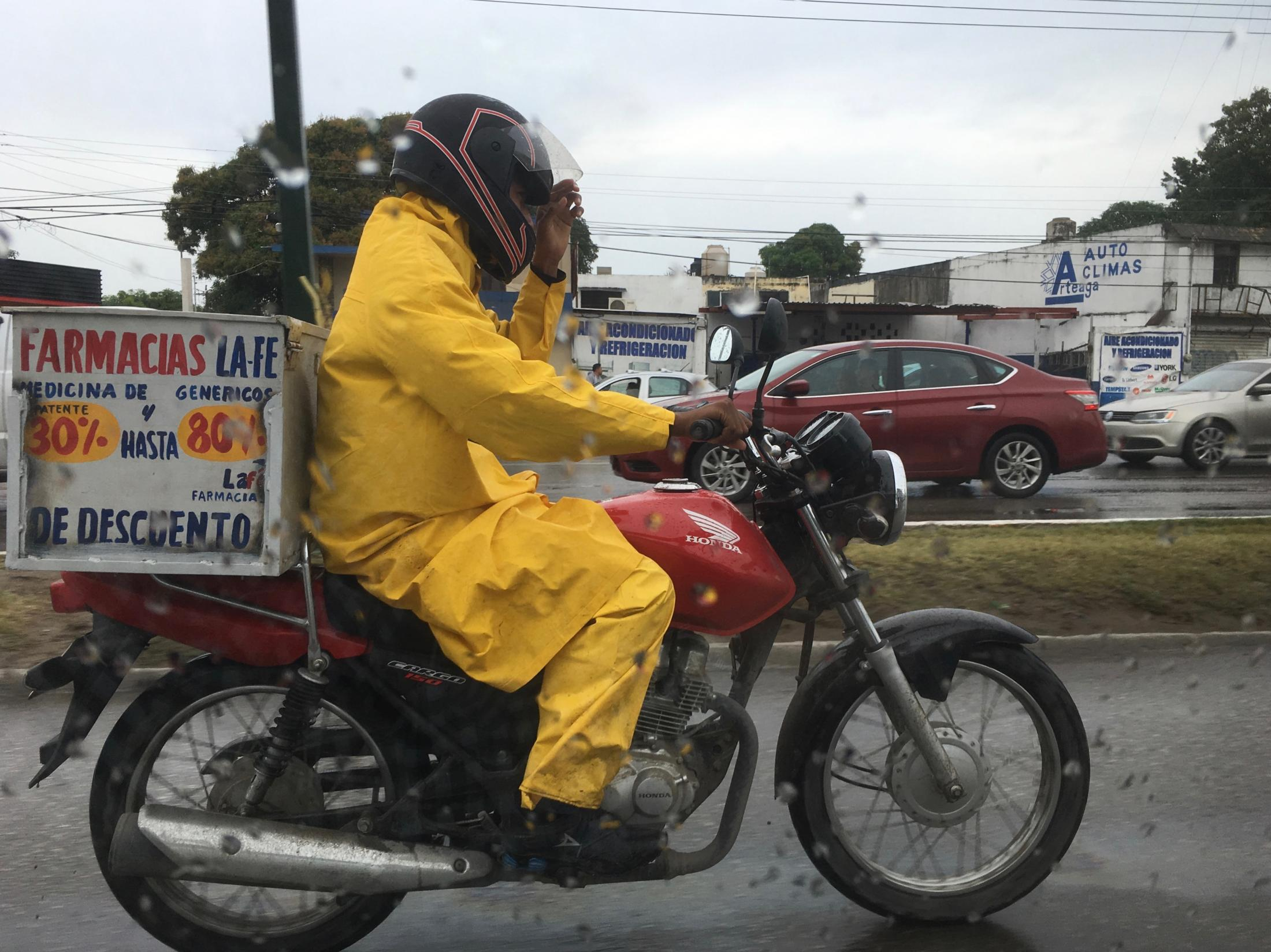 Tampico, Tamaulipas México. 2018. A pharmacy's delivery driver wears bright yellow gear to protect himself from the rain. I was on my home at noon from morning classes at my university.