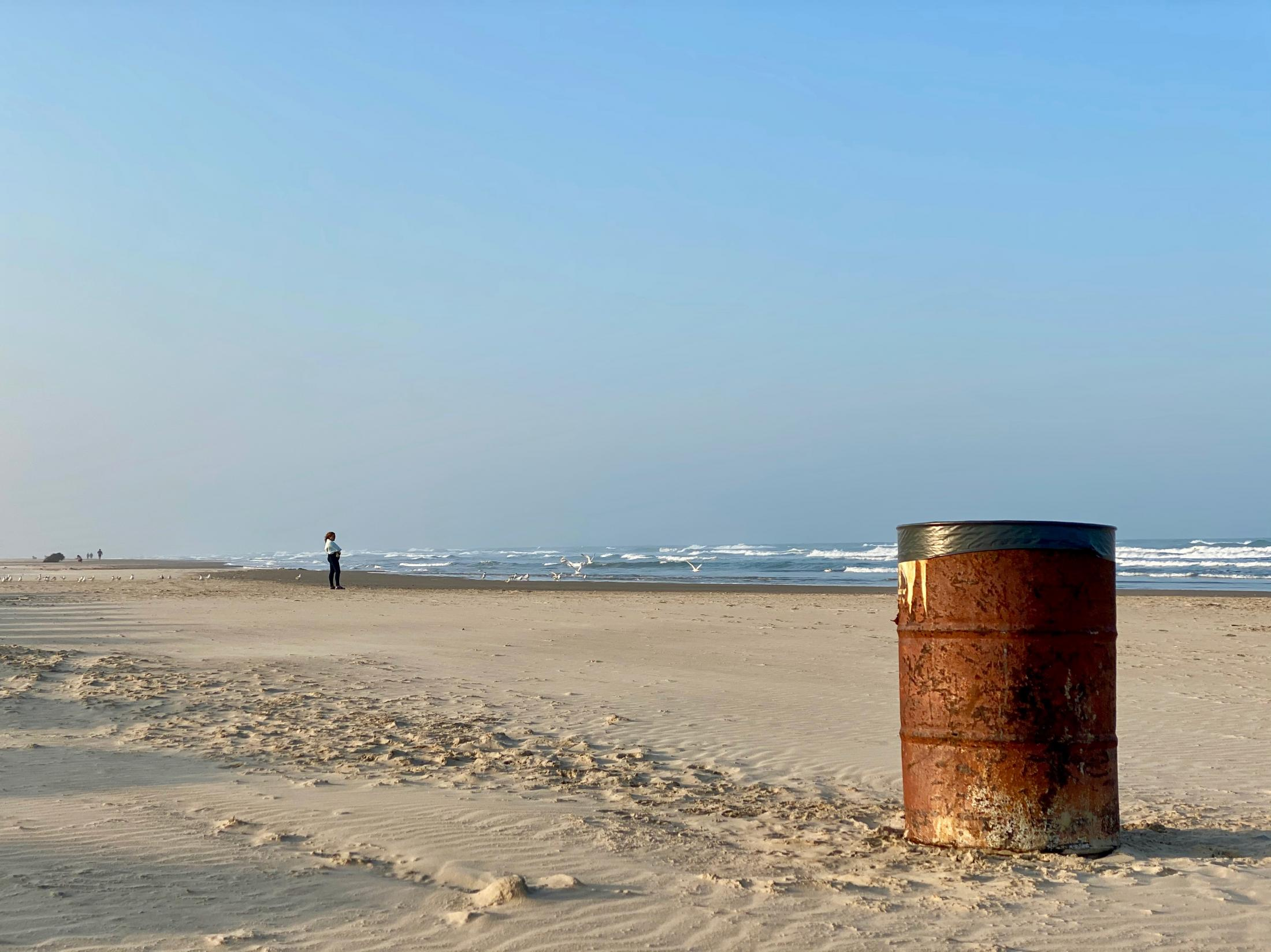 Playa Miramar, Tamaulipas, México. 2020. A trash bin sits on the sand while at a distance a lady gazes the water of the Gulf of Mexico. I was spending the windy afternoon at the beach with my girlfriend. We listened to our favorite music, drank beer, and had a henna tattoo of a sun drawnon one of each other's wrists.