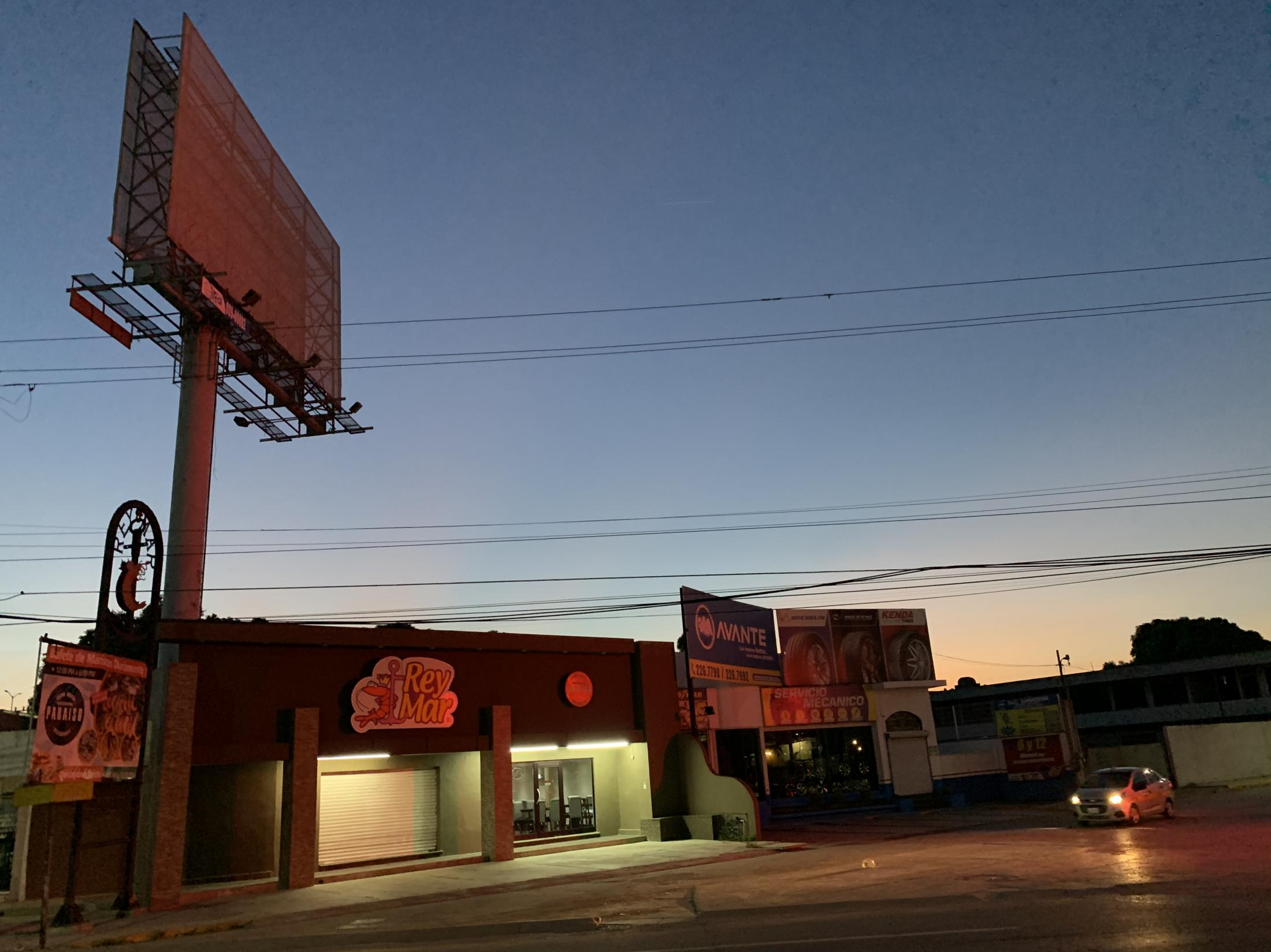 Altamira, Tamaulipas, México. 2019. Small commercial space and billboard with bright red light reflected on it. I was forced to walk more than regular to my university because I had not been paying attention and missed thebus stop where I got off.