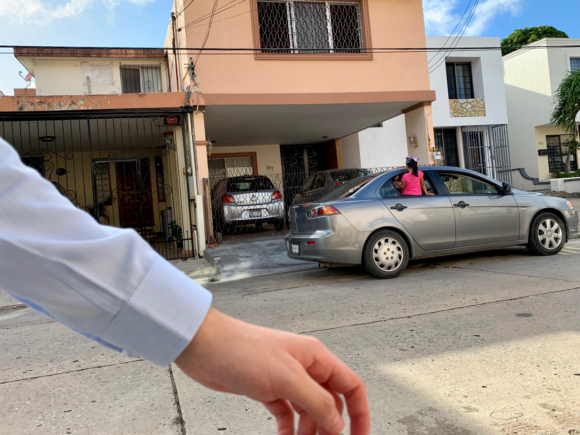 Tampico, Tamaulipas México. 2019. Arm and hand get in the way of the image of a little girl sitting on her window looking at the house next to her. I had just finished working and was walking back home.