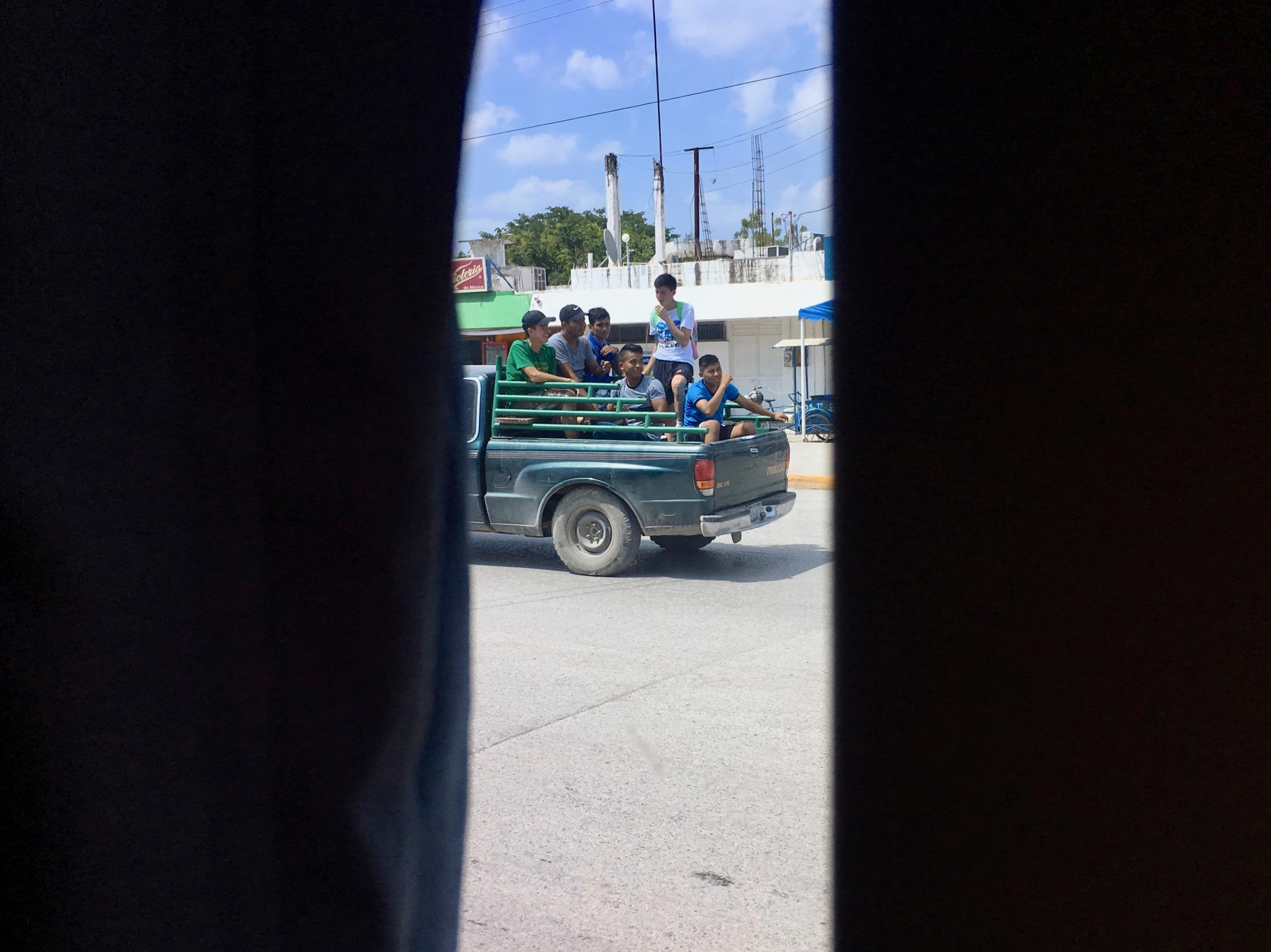 Estación Manuel, Tamaulipas, México. 2017. View from a bus to the back of a truck loaded with people. I was traveling back to where I live from visiting my parents during summer break.