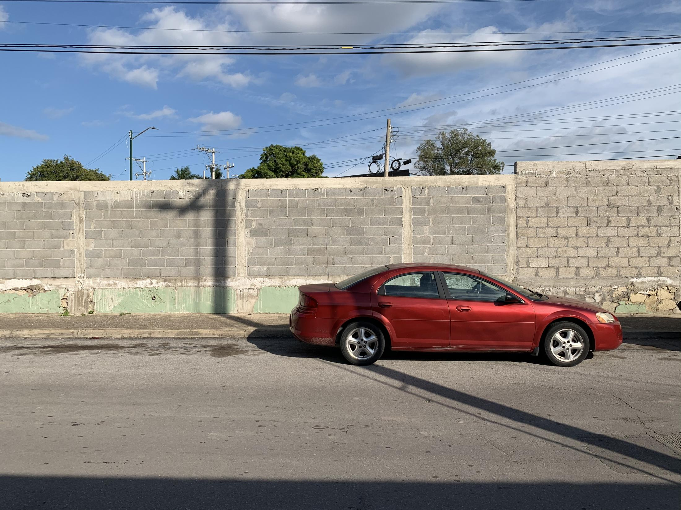Tampico, Tamaulipas México. 2019. A parked red car next to a brick wall from a construction site. This is the street I walked every other day during one semester to go to work.