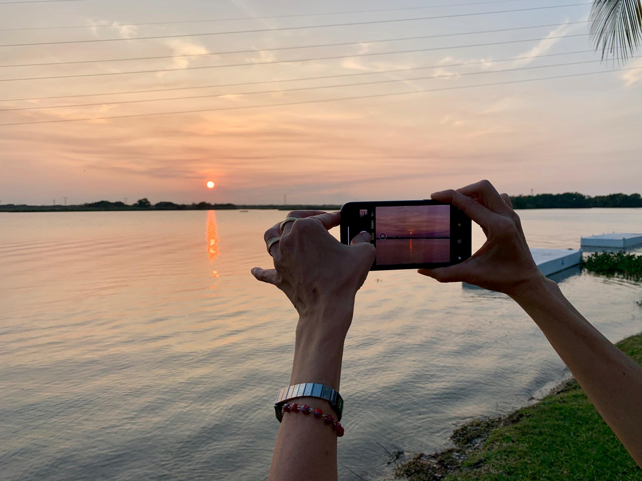 Tampico, Tamaulipas México. 2019. Mother taking a picture of one of many beautiful sunsets that can be appreciated at this lagoon.