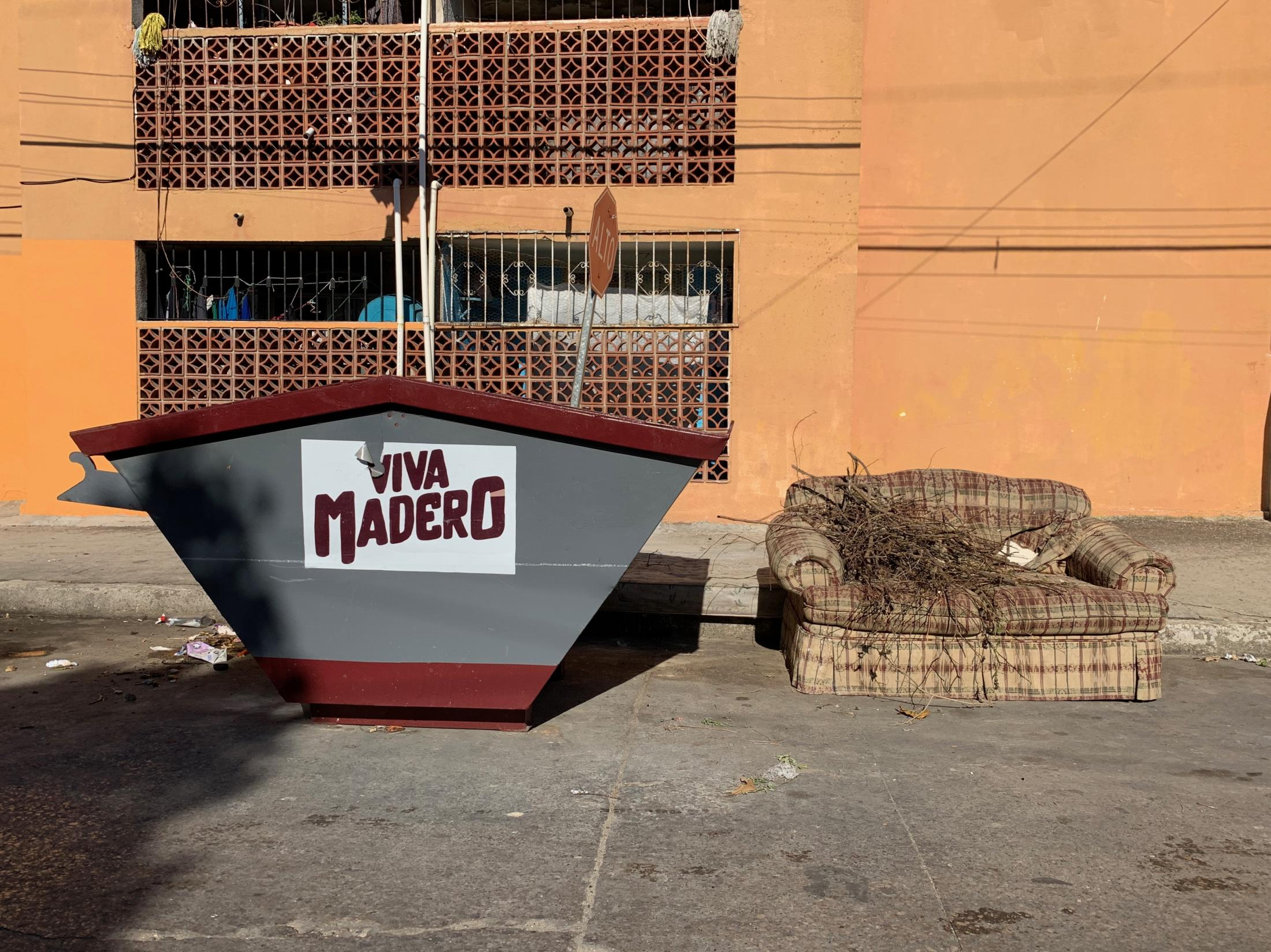 Ciudad Madero, Tamaulipas, México. 2019. A couch with branches and city owned trash container sit together on the corner of a street. Several days later the couch was gone. I was driving around the city with my girlfriend.