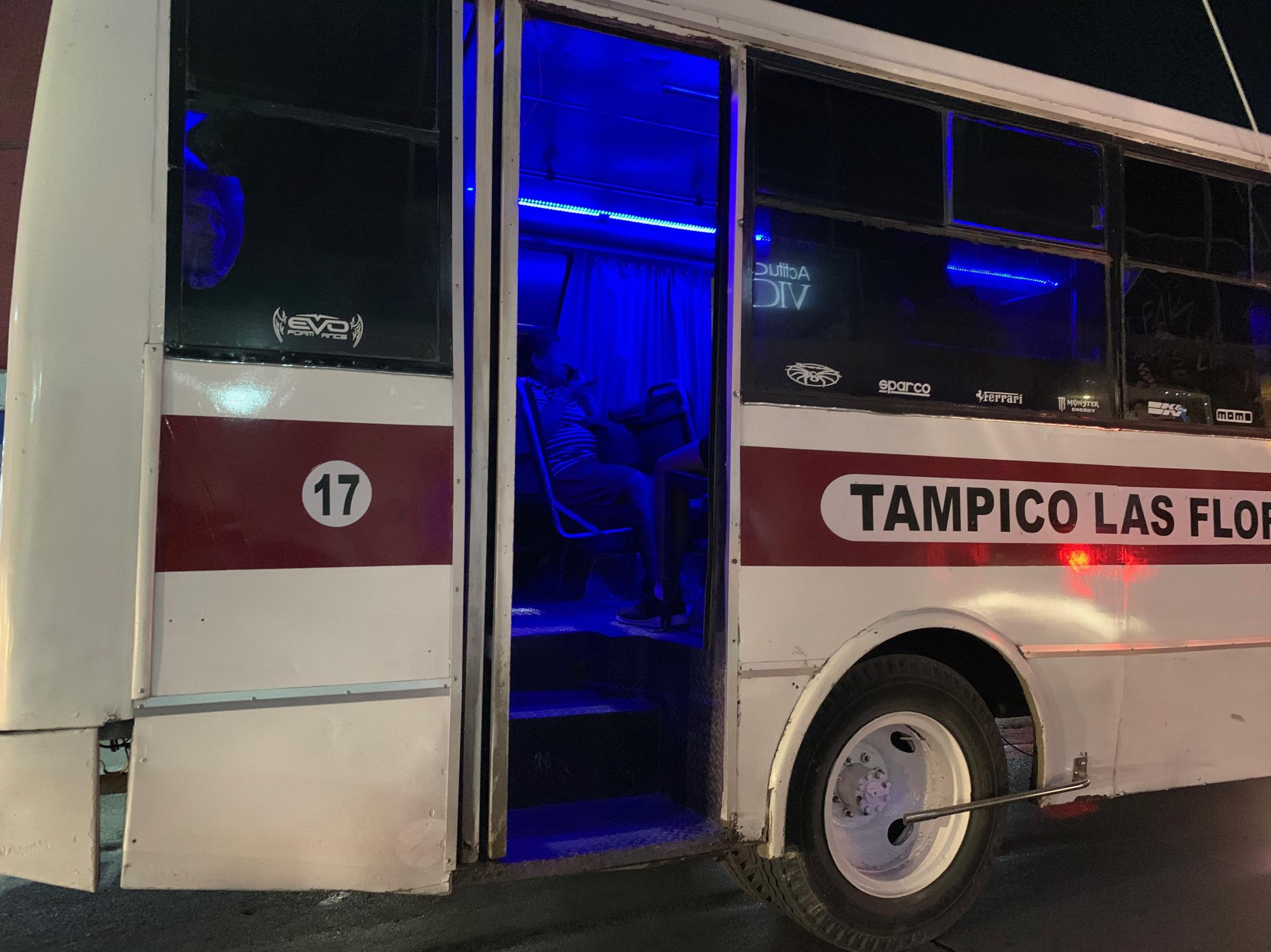 Ciudad Madero Tamaulipas,México. 2019. A lady talks on the phone and a man looks outside his window illuminated by the blue neon lights in interior of a public bus at night. This is a common sight in many Mexican cities. I was driving from the beach to my house.