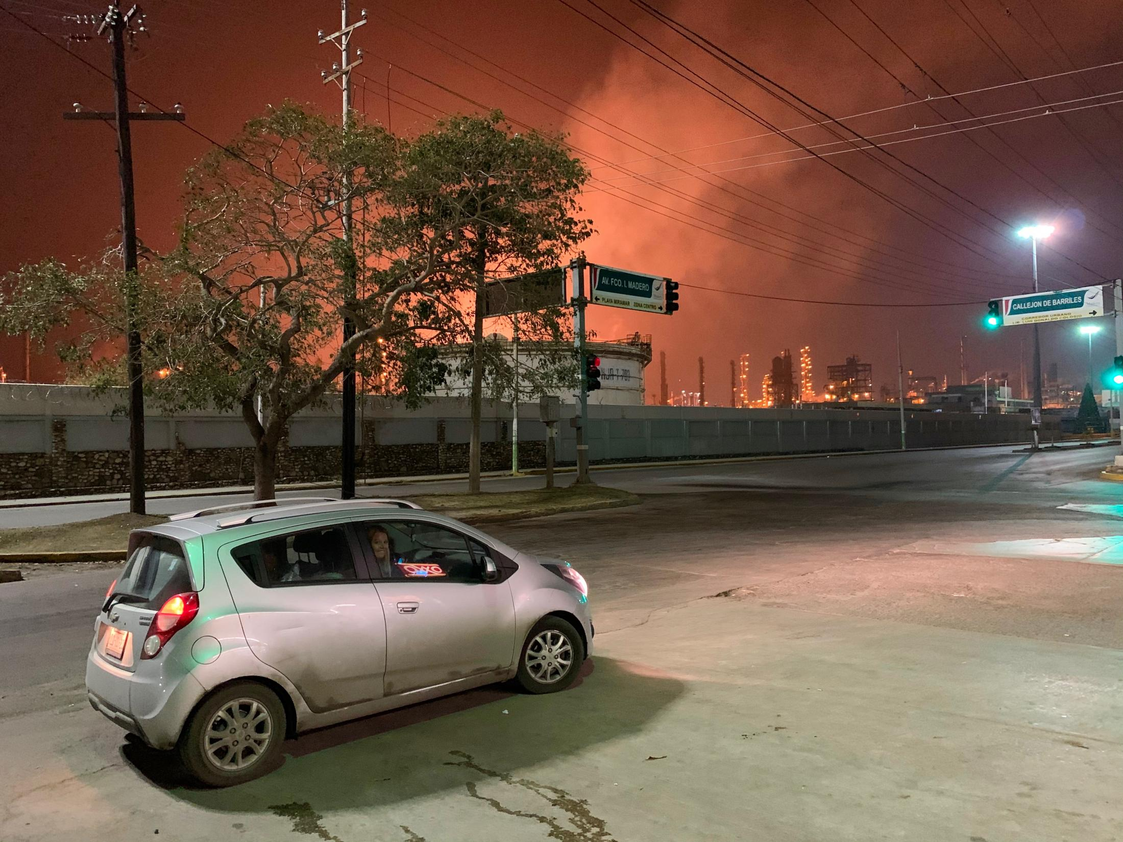 Ciudad Madero, Tamaulipas, México. 2019. My girlfriend's mother smiles from her car next the local refinery at night. My girlfriend's father drives the car while pretending to leave me behind as a joke. I was on my way to my girlfriend's house after spending the afternoon in a karaoke bar with them.