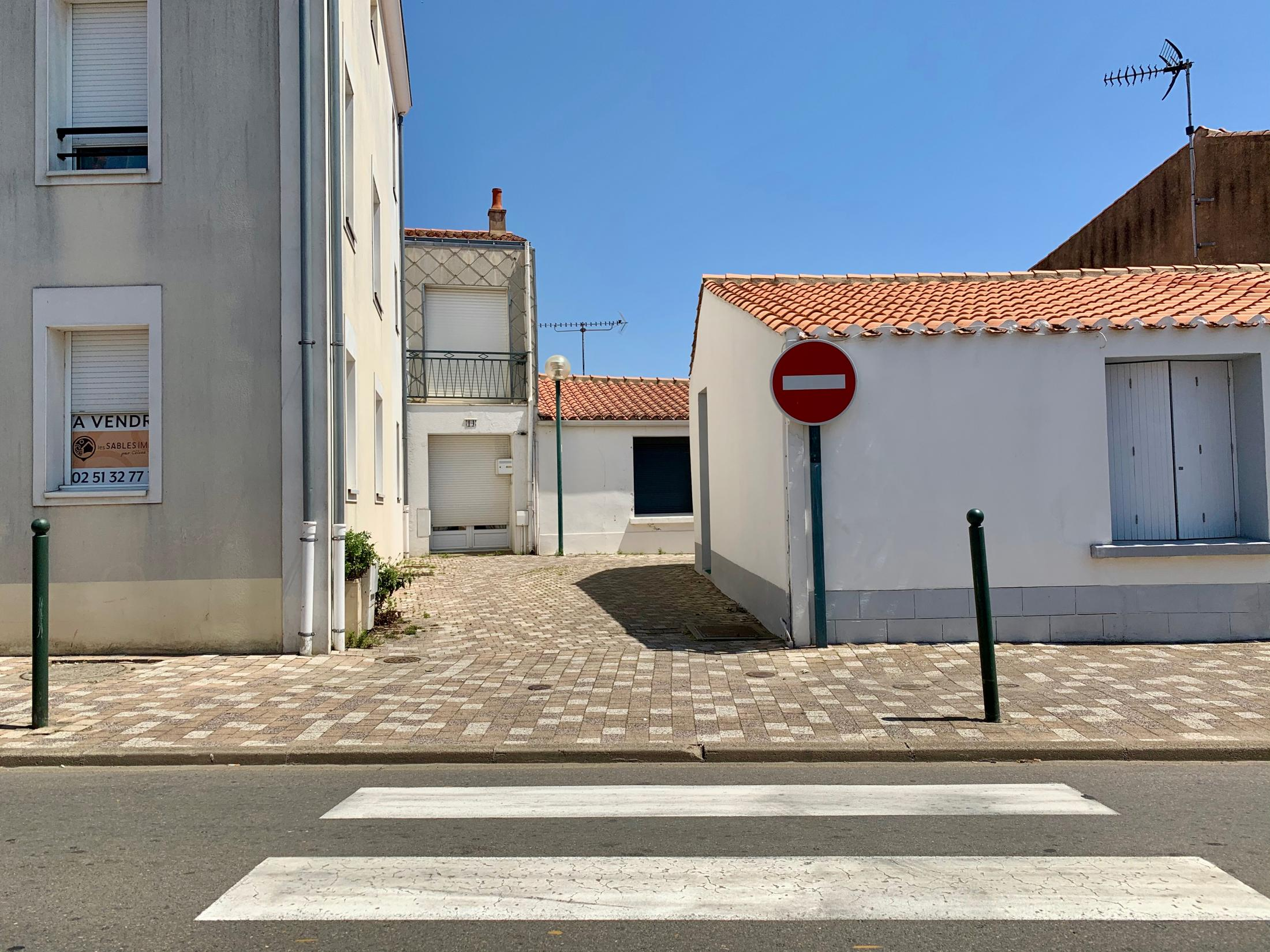 Olonne-sur-Mer, Pays de la Loire, France. 2019. Several buildings with northwestern french design. The white walls reduce the heat in the buildings. A friend I was visiting was showing me around his town.
