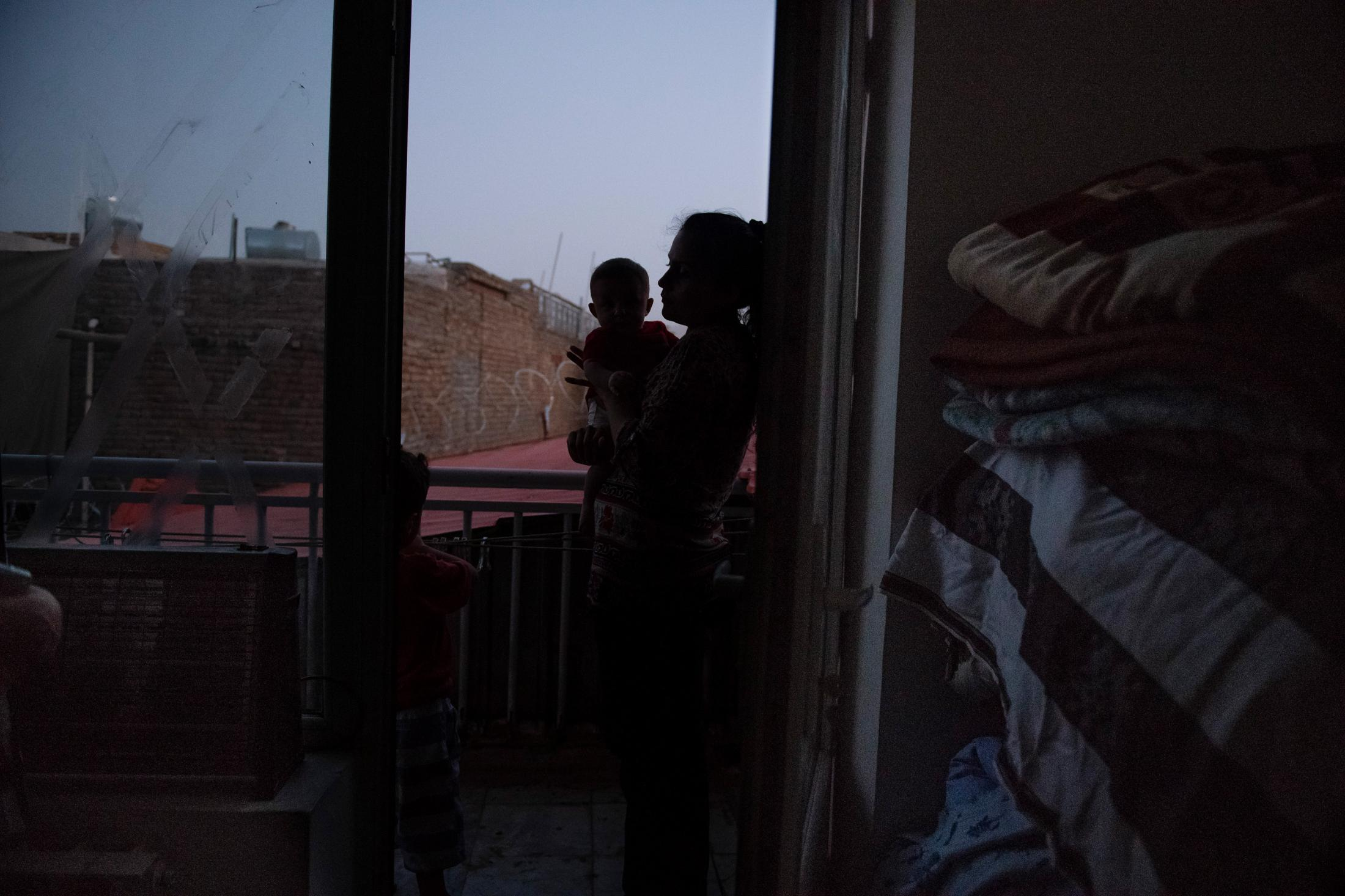 "KABUL | AFGHANISTAN | 8/10/18 | Mashal (26) takes her 3 year old son, Benyamin, to the balcony every time he asks after his father. Mashal points out to a star: ""Your father is resting there"". Everyday, ever since the death of her husband, Sabawoon (27), Benyamin starts acting out around the time his father would arrive home in the afternoon and it is a daily struggle for Mashal, who was 8 months pregnant at the time of his death, to keep her son calm and occupied. Sabawoon, a journalist for Azadi Radio, was killed in a double suicide blast in the Afghan capital on April 30, 2018. It was the deadliest single attack involving journalists in Afghanistan since at least 2002 which took the lives of 9 journalists. Kiana Hayeri for the New York Times"