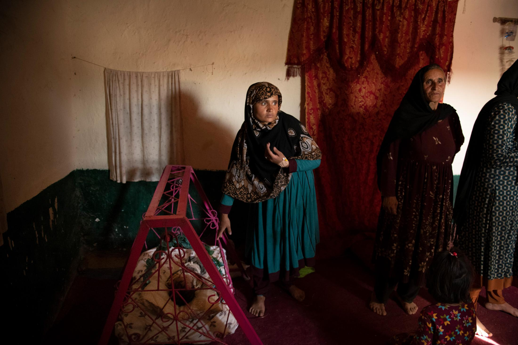 DOAGU VILLAGE | AFGHANISTAN | 8/27/18 | Fatana (24) swings the cradle of her 46 day old daughter, Esraa, in an attempt to put her to sleep. She was 5 months pregnant when her husband, Amanat Khan (27) and an ANP officer, was shot in fightings against Taliban in Niazi Village, not too far from their home village. Kiana Hayeri for the New York Times