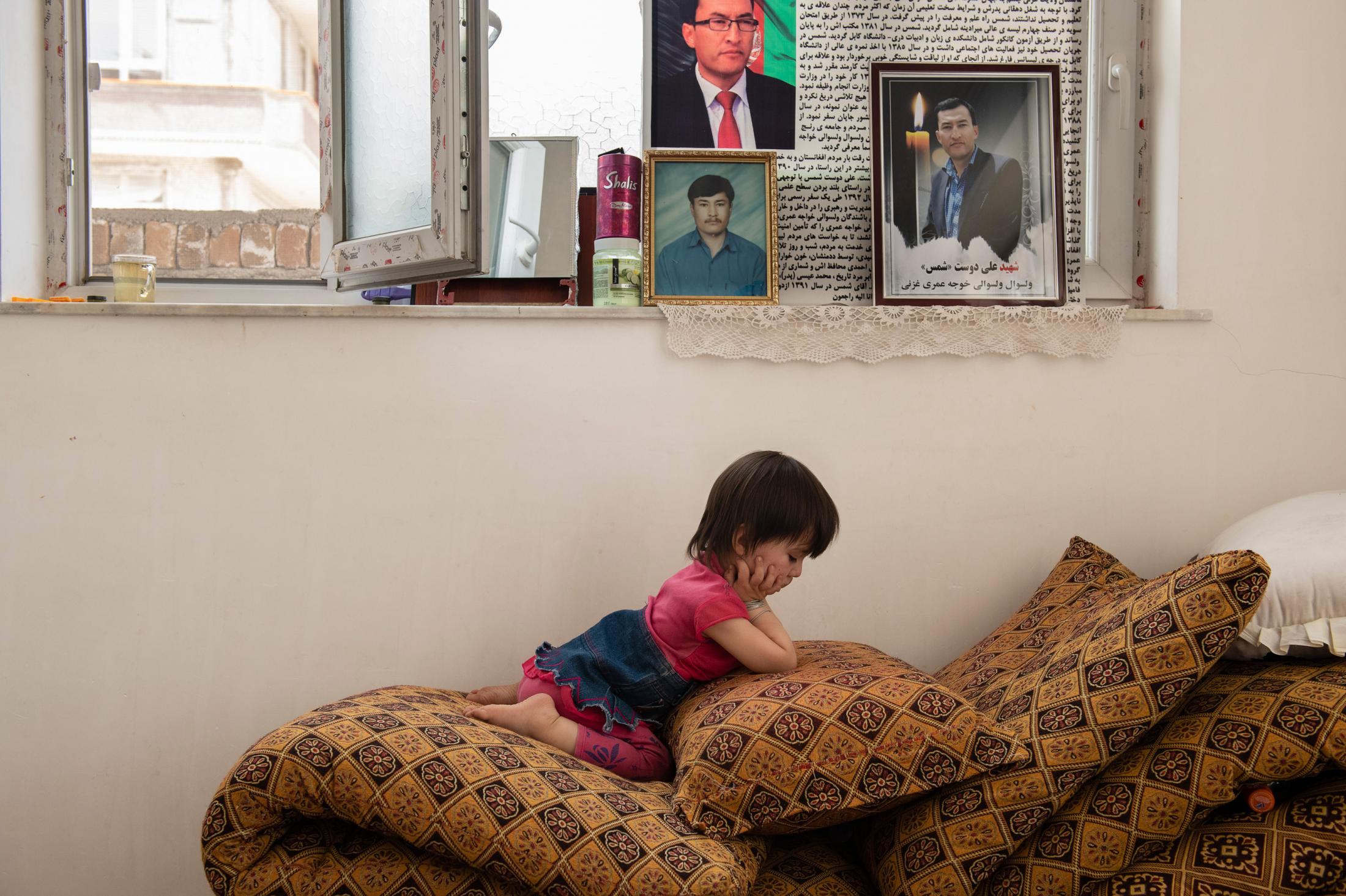 "KABUL | AFGHANISTAN | 7/26/18 | Sofia (2) plays quietly at her favorite corner of the house where a pile of tushaks beneath the photos of her father, serve her as a slide. Her father, Shams (37) was killed 3 months earlier on her birthday. Unable to fully comprehend his departure, in early days, Sofia restlessly asked for her father. Recently, she's started calling her uncle ""dad"". Sofia is expecting a baby sister any day. Kiana Hayeri for the New York Times"