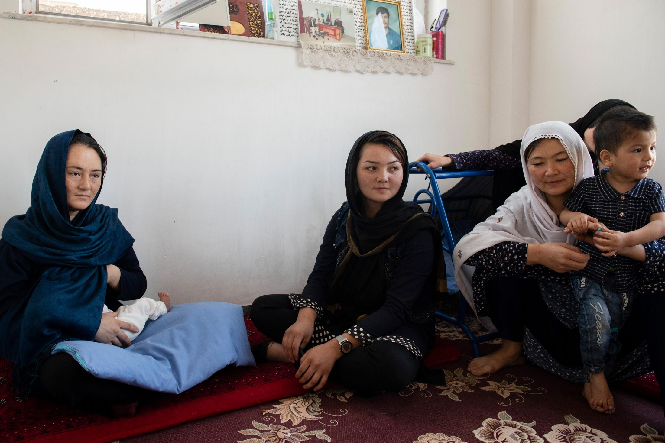 KABUL | AFGHANISTAN | 8/25/18 | Rahila (22) breastfeeds her 22-day-old daughter, Shamsia, who was named after her father Shams. Her sister, Reyhana, and her father-in-law had traveled all the way from their village in Ghazni to visit Rahila and her newborn daughter. While 5 months pregnant, Rahila's husband, Shams (37), was killed by Taliban in Ghazni province. Kiana Hayeri for the New York Times