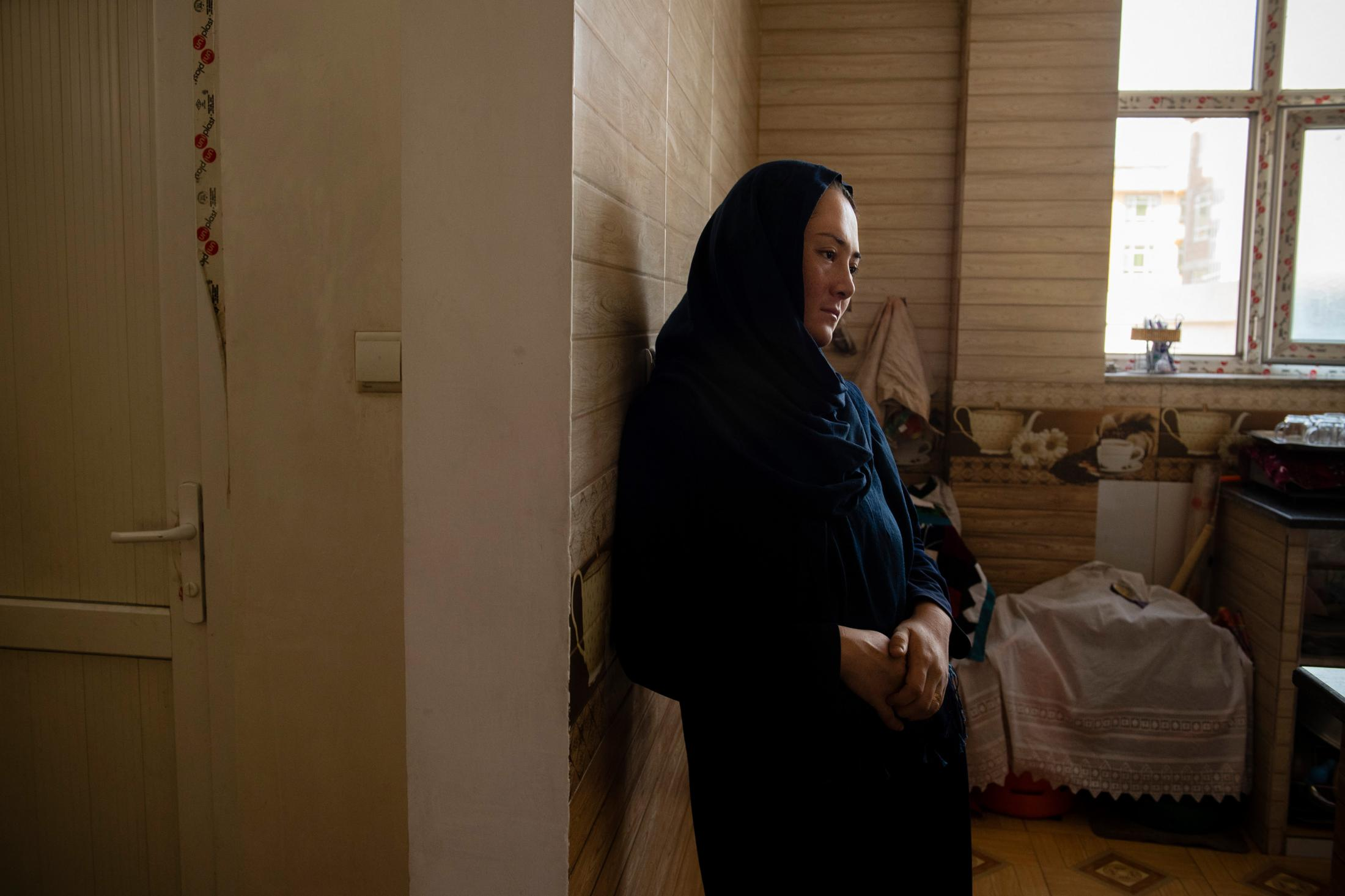 KABUL | AFGHANISTAN | 8/25/18 | Rahila (22) quietly stands by her kitchen, 22 days after she gave birth to her daughter, whom they named Shamsia, after her Father, Shams. On Sofia's 2nd birthday, her father, Shams (37), was killed by Taliban in Ghazni province. At the time, Rahila was 5 months pregnant. Kiana Hayeri for the New York Times