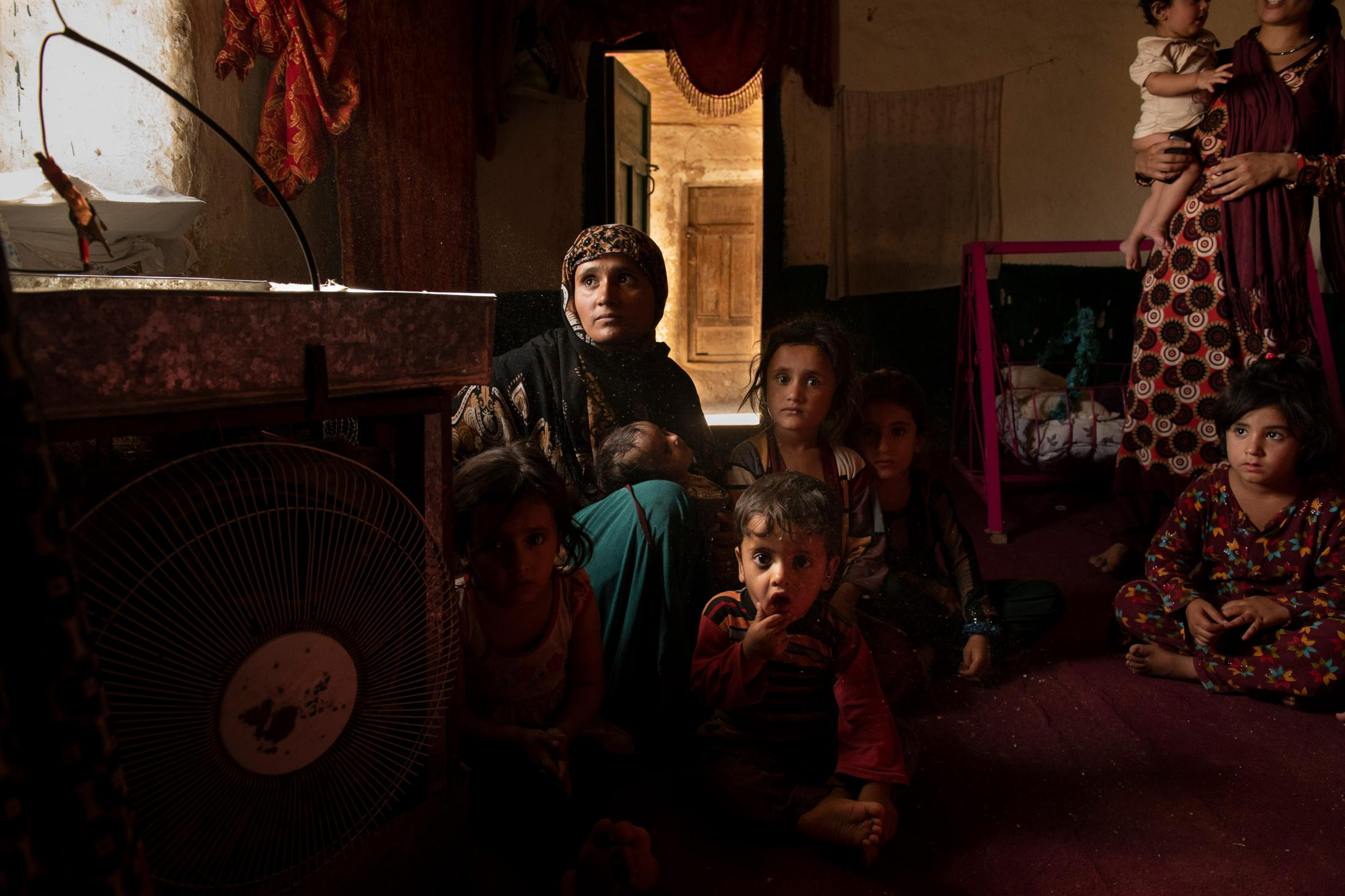 DOAGU VILLAGE | AFGHANISTAN | 8/27/18 | Fatana (24) sits with her 4 children inside their small room at her in-laws that she and her late husband used to live in. She was 5 months pregnant when her husband, Amanat Khan (27) and an ANP officer, was shot in fightings against Taliban in Niazi Village, not too far from their home village. Kiana Hayeri for the New York Times