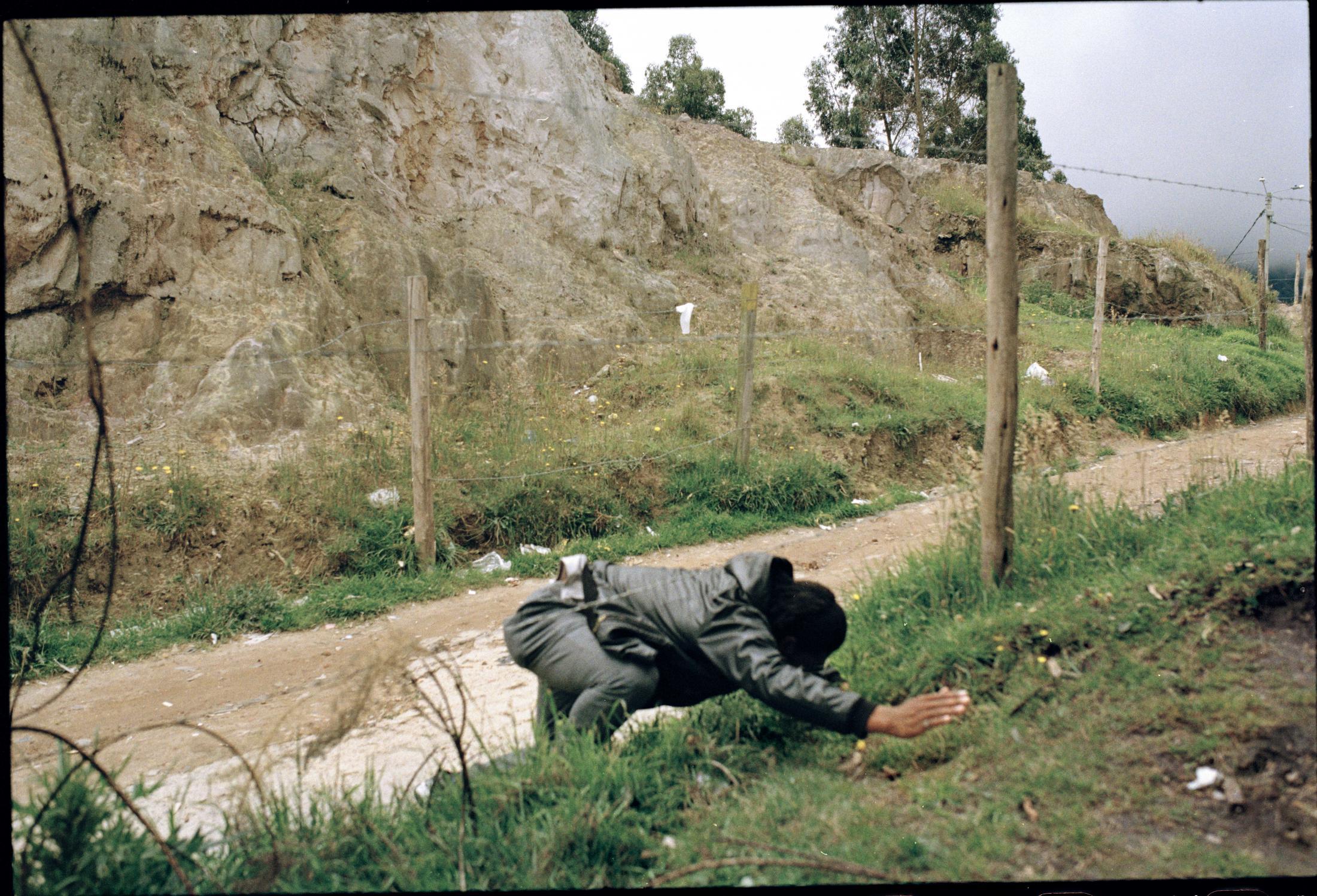 Arley Estupiñán imita el movimiento que hizo en la madrugada del 13 de enero de 20178 cuando fue víctima de un atentado con arma de fuego mientras regresaba a su vivienda en el barrio San Germán, en la localidad de Usme, al norte de Bogotá. Al escuchar los disparos y ver el destello del arma colina arriba, Estupiñán saltó una cerca de puas y rodó cuesta abajo. Uno de los tres proyectiles que le dispararon alcanzó a rozar su brazo.