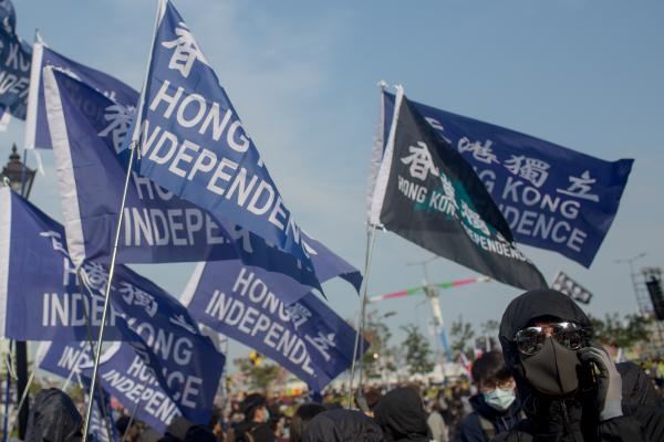 A protester who was part of a group carrying Hong Kong independence flags and using black bloc tactics answers a phone call at Edinburgh Place in Central Hong Kong on January 12, 2020, during the Karma to Commies pre-march assembly.