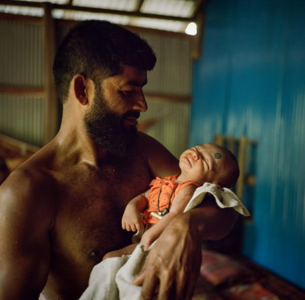 Abul Kalam, a fisherman and laborer, poses for a portrait with his 17-day-old son at the time in Ayeshabag, Bangladesh. In this district of Bangladesh, located near the mouth of the Bay of Bengal, many families are involved in fishing. But their livelihoods are at stake with extreme weather patterns, two deadly cyclones hit this region in 2019. Copyright © Sara Hylton/National Geographic, 2019