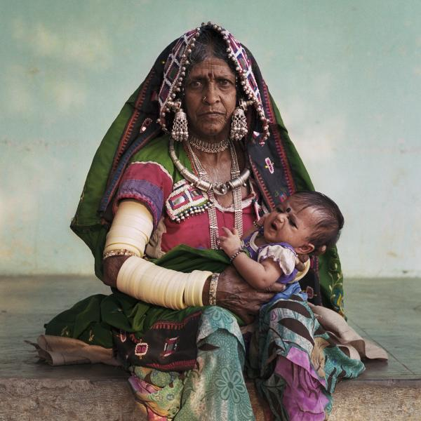 Biki Malavath, holds her great granddaughter, nicknamed Milky, in Laxmapur Thanda, a village in Telangana state, India. Laxmapur Thanda is a village of Lambadi people, a scheduled tribe considered one of India's more disadvantaged communities. Telangana has suffered from extreme weather patterns, with draught affecting farming families like Biki's. But a member of Biki's family, Yadav Bhavanth, was one of the first in his village to introduce a climate adaptive greenhouse that relies on 90 percent less water. Yadav's family has benefited from increased crop yields, and many others in the village are following suit. Copyright © Sara Hylton/Redux Pictures, 2018