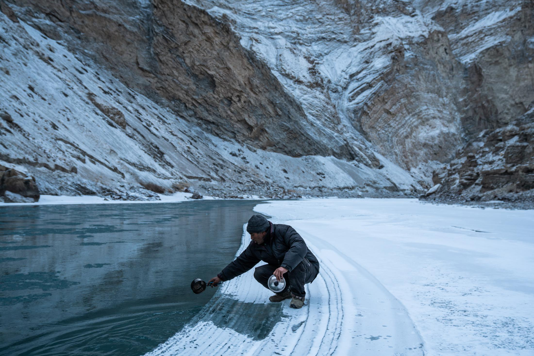 Collecting water from an unfrozen part of the river to boil for food.