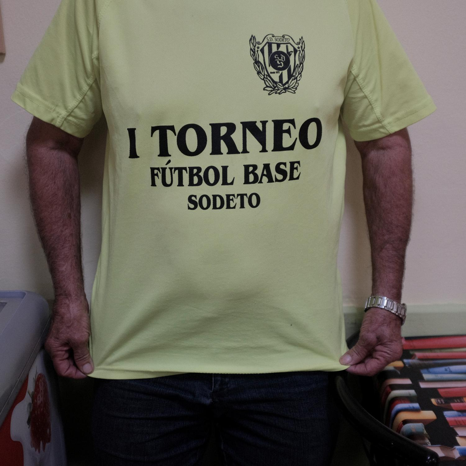 A retired farmer of Sodeto (Huesca), a settleds spot of no more than 200 inhabitants, showing a T-shirt of a football tournament. After the Spanish civil war in 1936, under Francisco Franco´s dictatorship, an agriculture reform was enforced leading to the building of more than 300 new towns all around Spain. This towns were populated with people coming from other rural impoverished areas but most of them are in high risk of disappearing because the new generations are moving to cities and abandoning these areas. Copyright: Spanish photojournalist Andoni Lubaki.