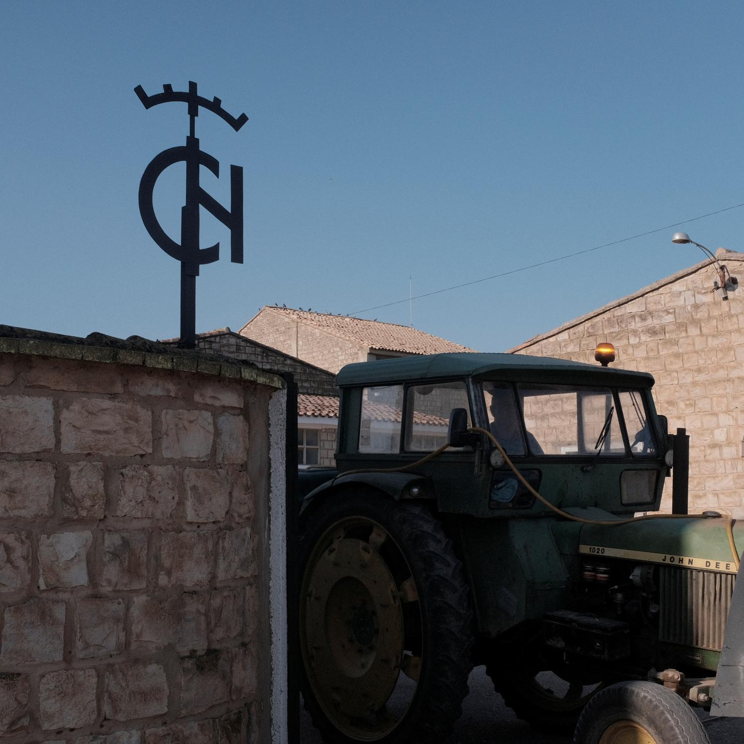 A tractor in the door of the Agricultural Cooperative of Bardenas (Zaragoza) a settlers town near Egea de los Caballeros. The logo of the institute of colonization is on the door. After the Spanish civil war in 1936, under Francisco Franco�s dictatorship, an agriculture reform was enforced leading to the building of more than 300 new towns all around Spain. This towns were populated with people coming from other rural impoverished areas but most of them are in high risk of disappearing because the new generations are moving to cities and abandoning these areas. Copyright: Spanish photojournalist Andoni Lubaki.