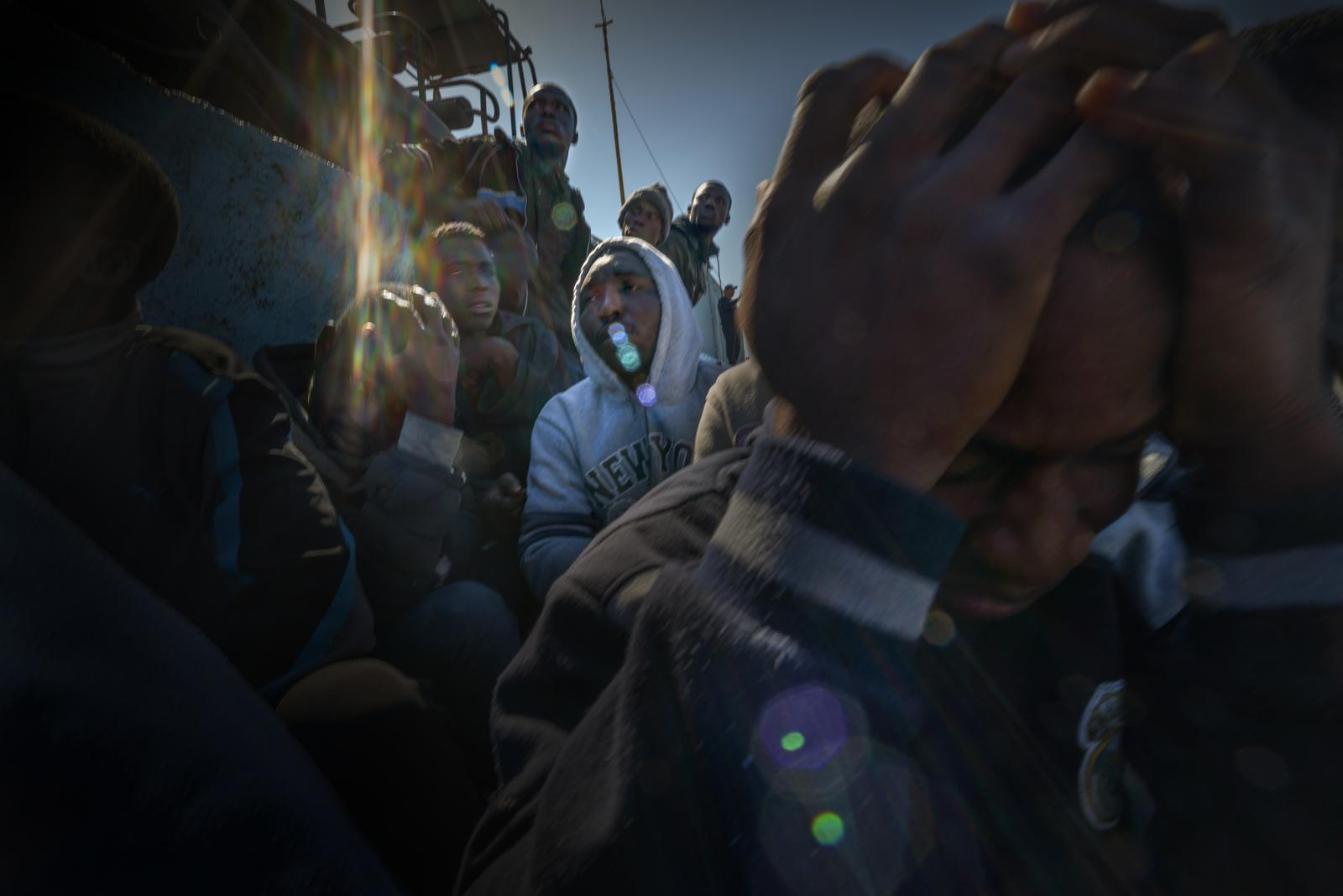 Intercepted by the Libyan Coast Guard just a few miles off the coast, refugees and migrants wait in the Port of Tripoli to be transferred to a detention centre; from there, they will be repatriated back to their home countries.