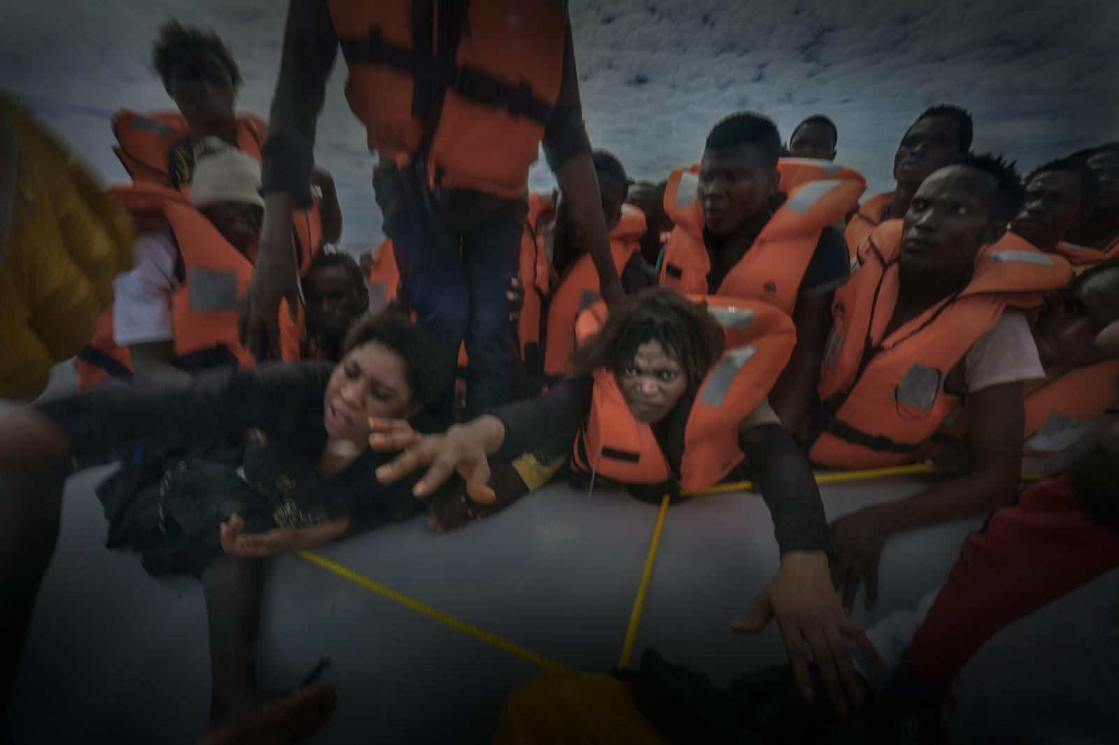 Sub-Saharan refugees and migrants desperately attempt to disembark from the inflatable boat in which they have travelled for several hours, and from which they are now being rescued on the Mediterranean Sea by members of the NGO Doctors Without Borders.