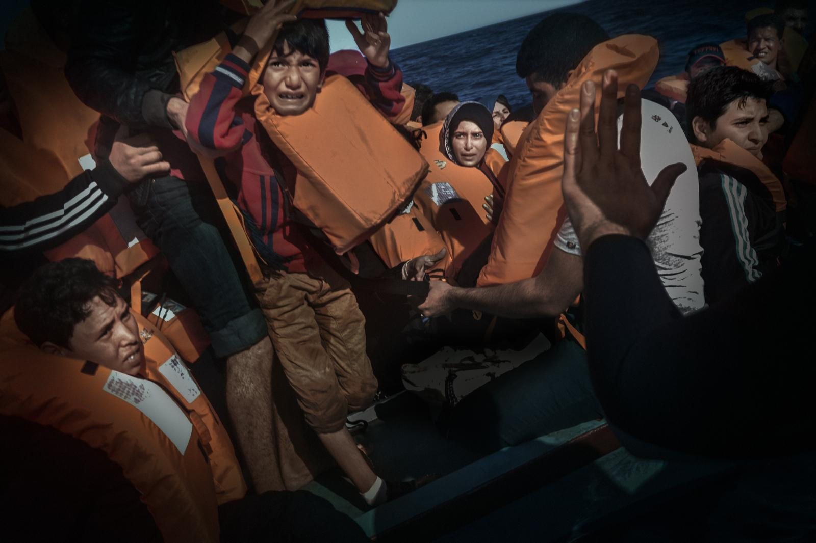A Syrian boy cries out in pure panic while a crewmember urges passengers to stay calm during a rescue operation on the Mediterranean Sea carried out by members of the NGO Open Arms.