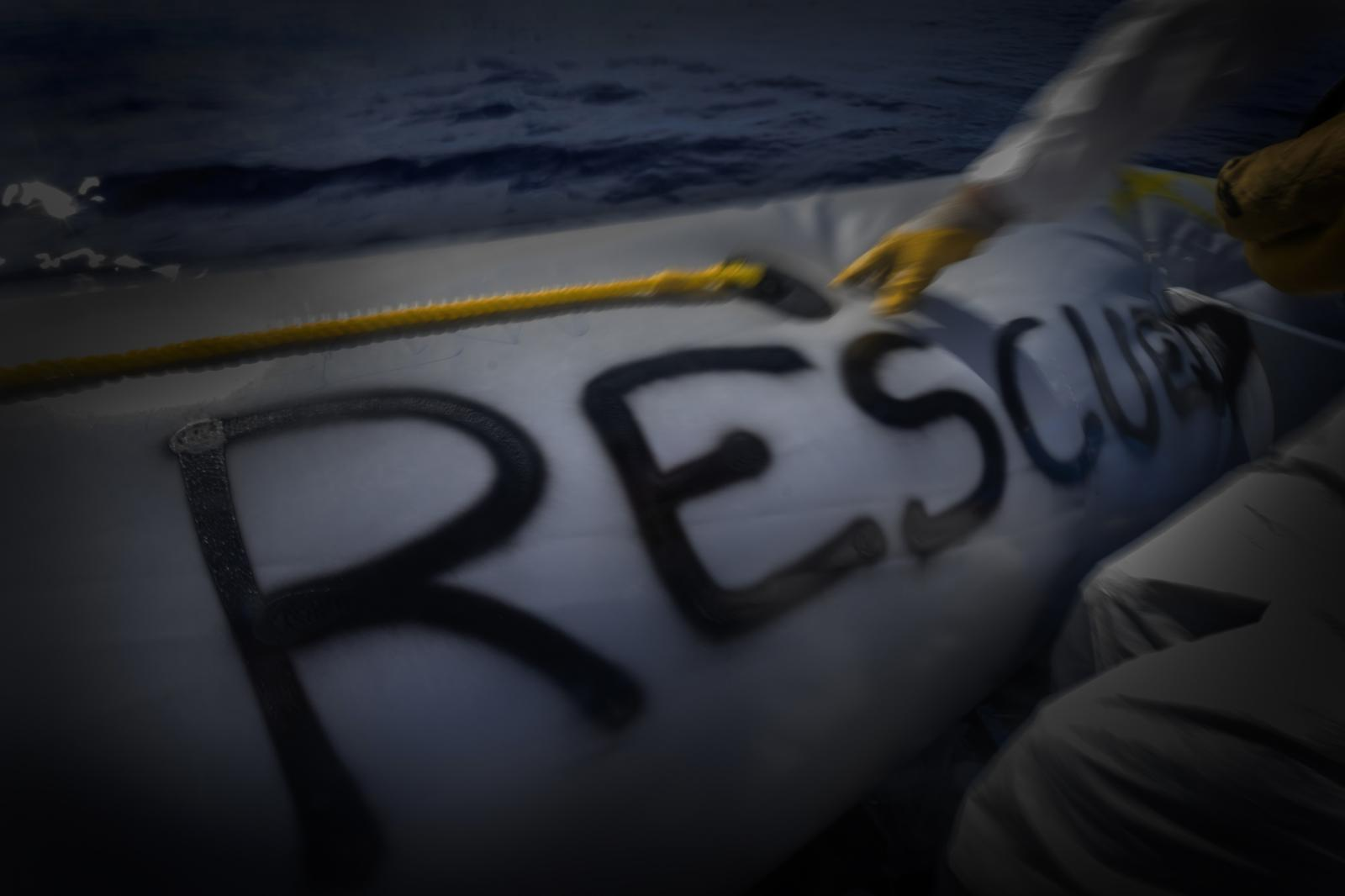 A member of the Doctors Without Borders crew spray paints the Word RESCUED on a now empty boat.
