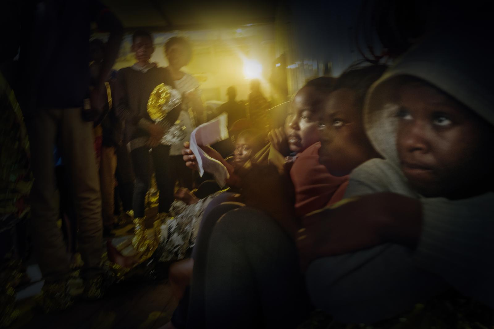 Refugees and migrants on board the Bourbon Argos while blankets and food are handed out for the first night on the passage to Italy.