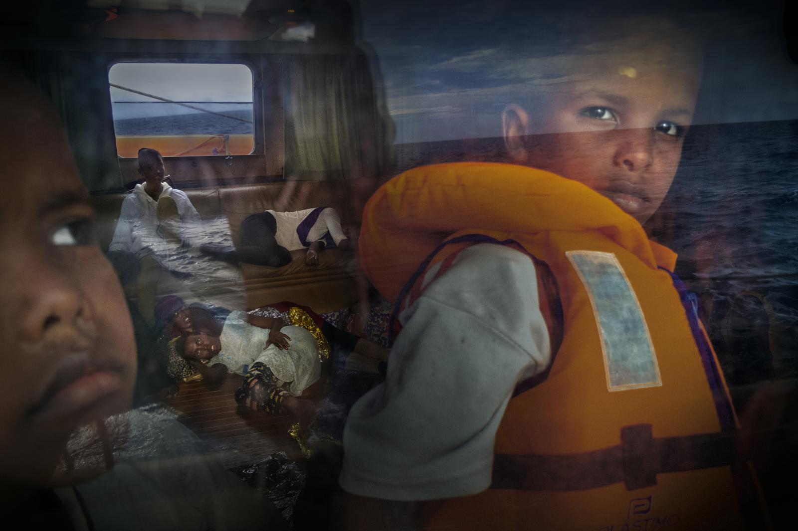 Samir, 8, from Somalia, looks out the window of the NGO Proactiva Open Arms rescue vessel Astral, while other refugees and migrants rest on their way to Lampedusa during a storm. With up to 65 km-per-hour winds, the storm, undoubtedly, would have killed them all. Libya, with its 1,770 kilometres (1100 miles) of shoreline plunged in chaos, has become an illegal immigration hub on the way to Europe. The migrants embark in rickety boats on hopeless crossings to Lampedusa, some 300 kilometres from the coast.