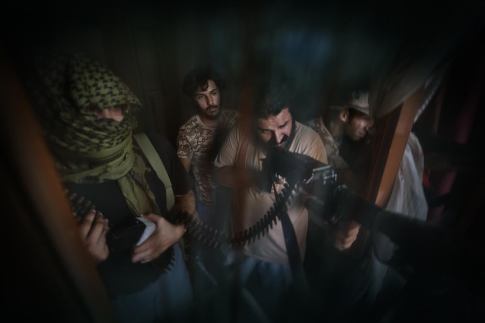 """""""Shelba"""" unit fighters, allied with the Libyan government and backed by the UN, aim at enemy positions on the front line in Tripoli's Salah al-Din neighbourhood (2014-2020)."""