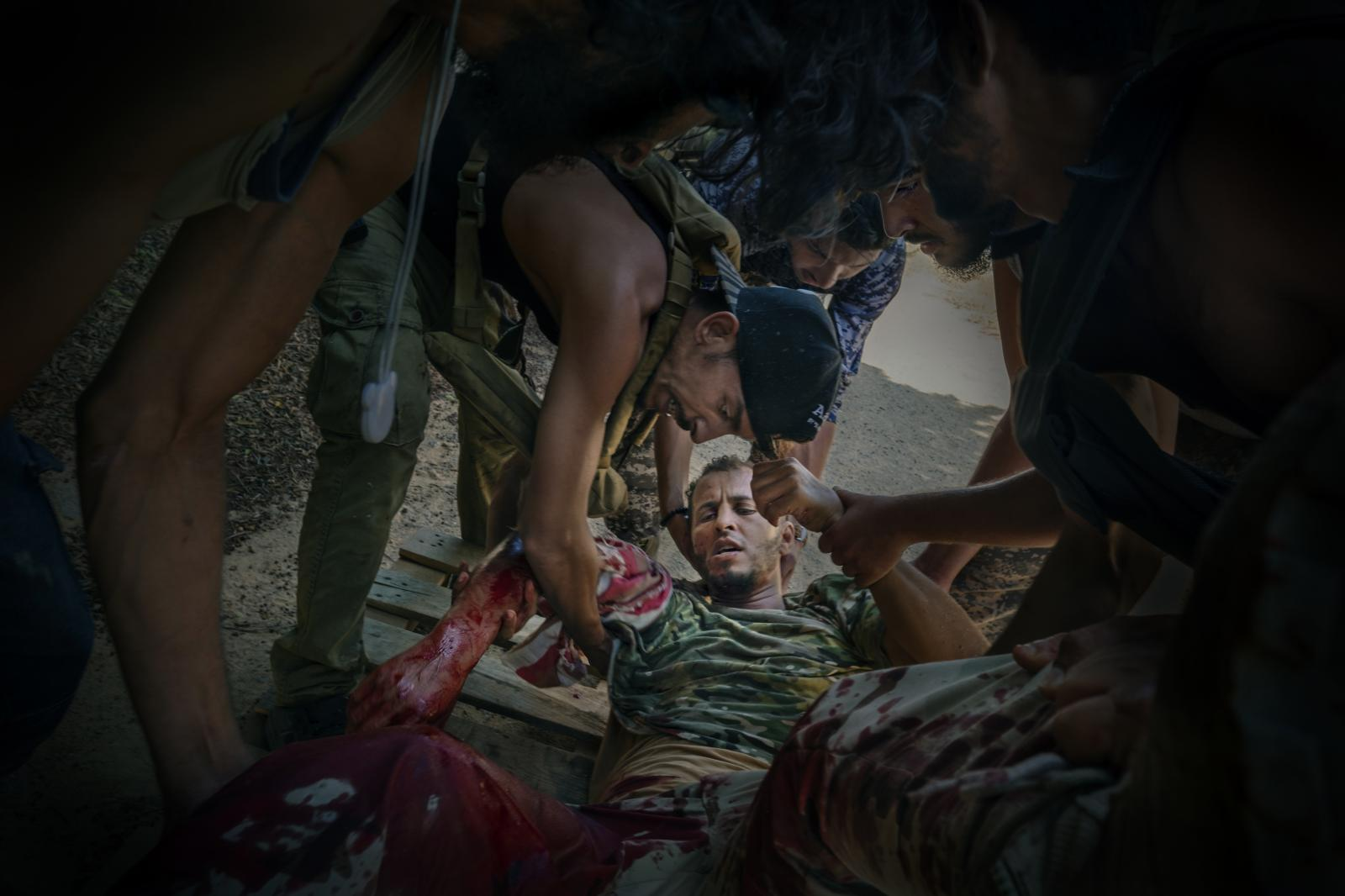 """A mortally wounded solider from the """"Shelba"""" unit, allied with the Libyan government and backed by the UN, is moved after being shot on the front line, in Tripoli's Salah al-Din neighbourhood. The fighting broke out in April 2019, when the self-proclaimed Libyan National Army under Field Marshal Khalifa Hafter launched an offensive to take Tripoli (2014-2020)."""