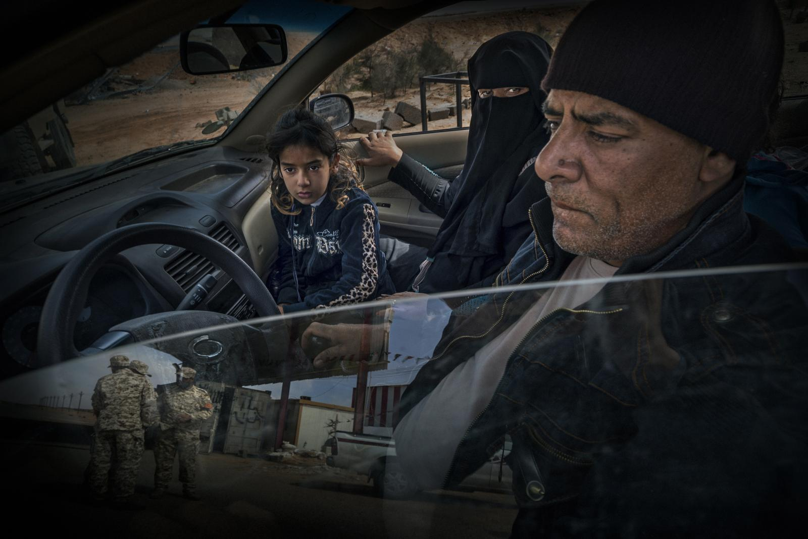 Family inside a car coming from Sirte, a city at that time controlled by ISIS. In the image, the military police checkpoint and Brigade 166, in Abu Qurayn, where ISIS launched a coordinated attack with the Albagla point, and which signalled the start of the Sirte campaign, can be seen (2016).