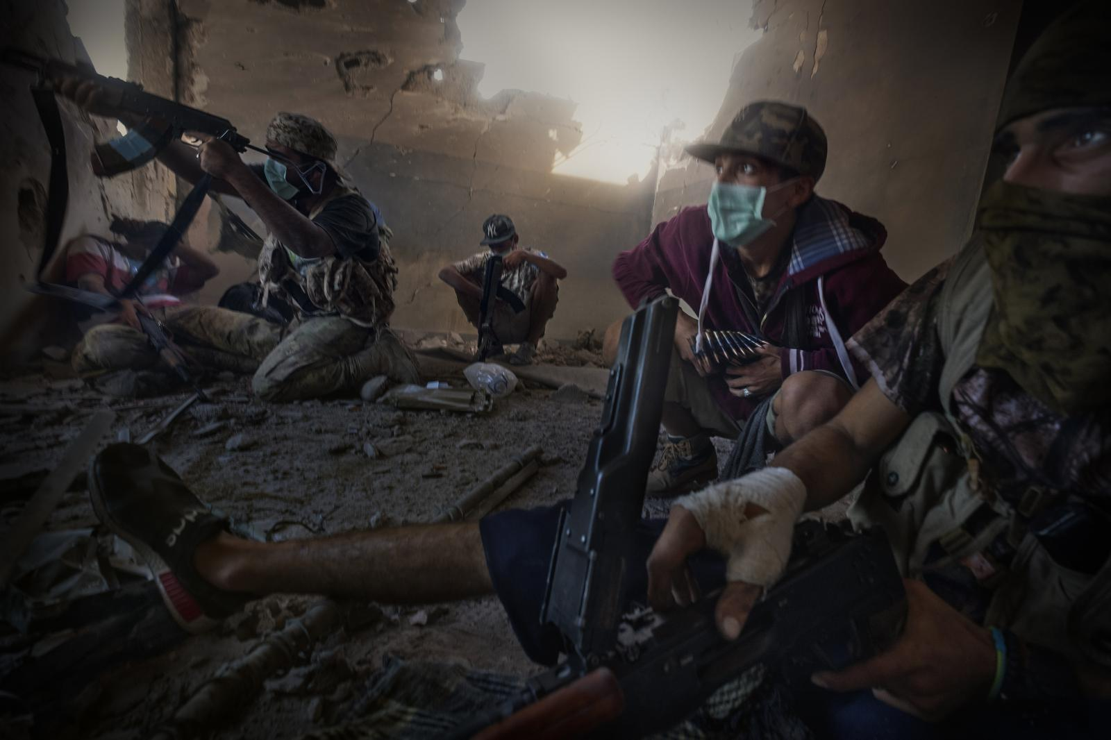 Soldiers use masks to be able breathe in the heavy gunpowder air produced by the multitude of shots fired inside a building during very intense and drawn-out fighting against ISIS, in Sirte (2016).