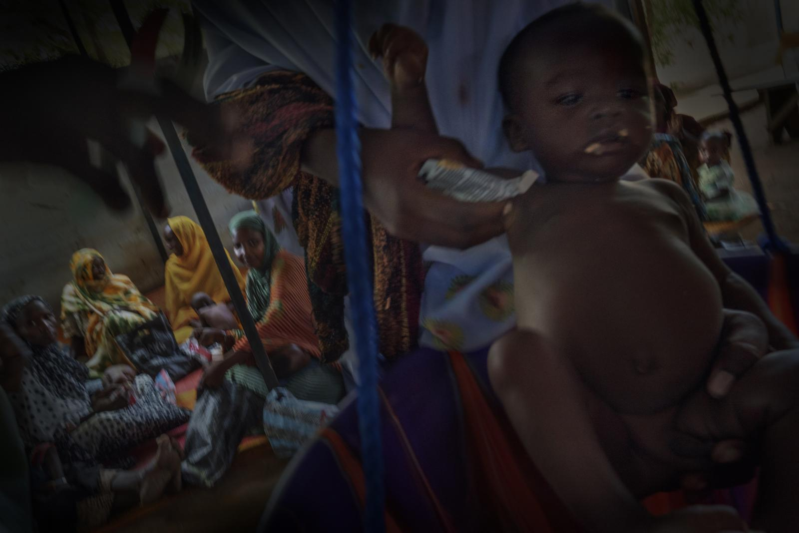 Members of the NGO Doctors Without Borders weigh a little boy in a mobile clinic in the region of Bokoro (Chad).