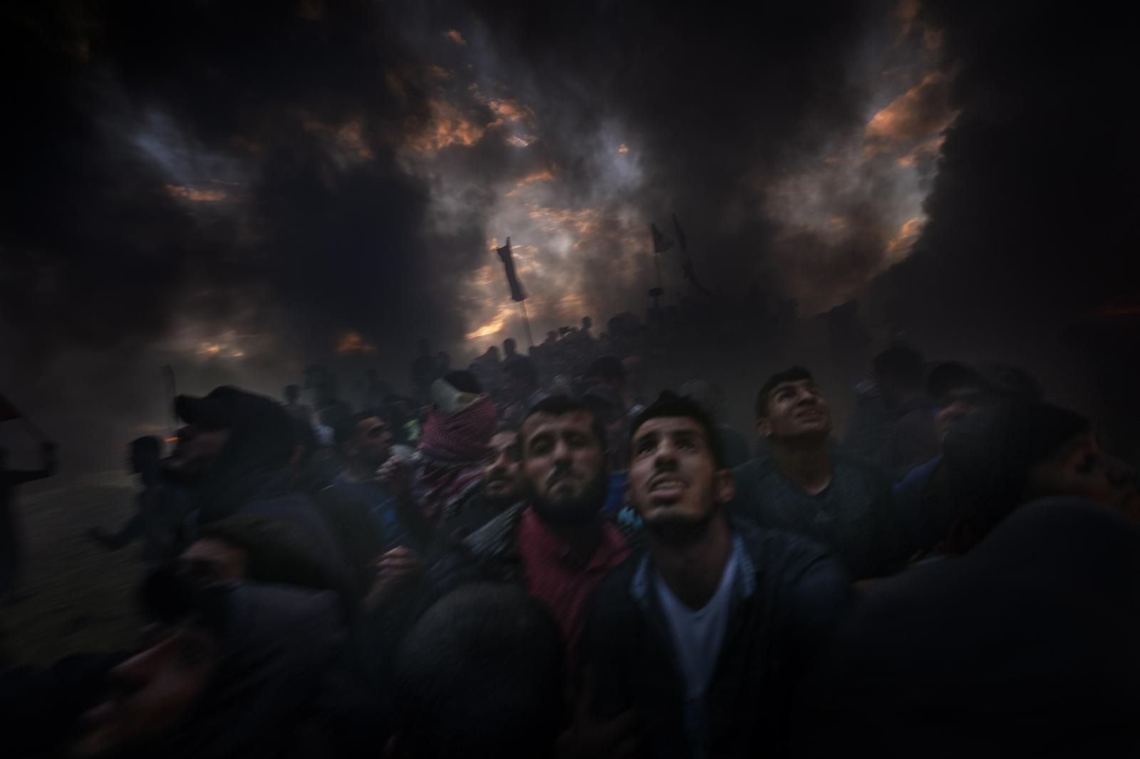 Palestinians enveloped in smoke from burnt tires look up at the sky in search of gas shells being fired at them. They try using the smoke to reach the limits of the fence, during the Great March; still, in each protest, the participants suffer a high rate of deaths and injuries (Gaza).