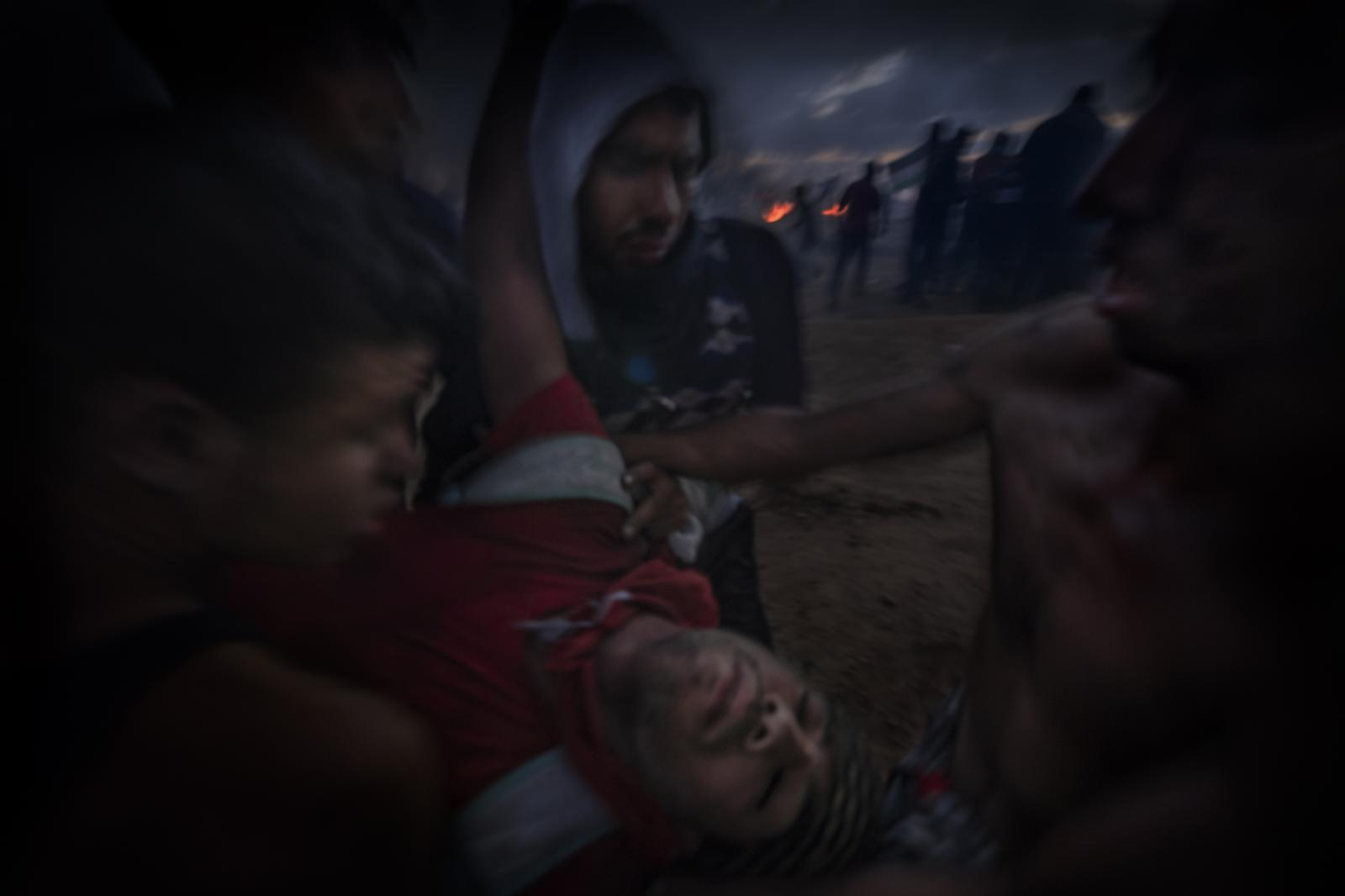 An unconscious Palestinian, wounded by a sniper on the front line of the fence, is quickly carried in his friends' arms. He died a short time later. (Gaza).