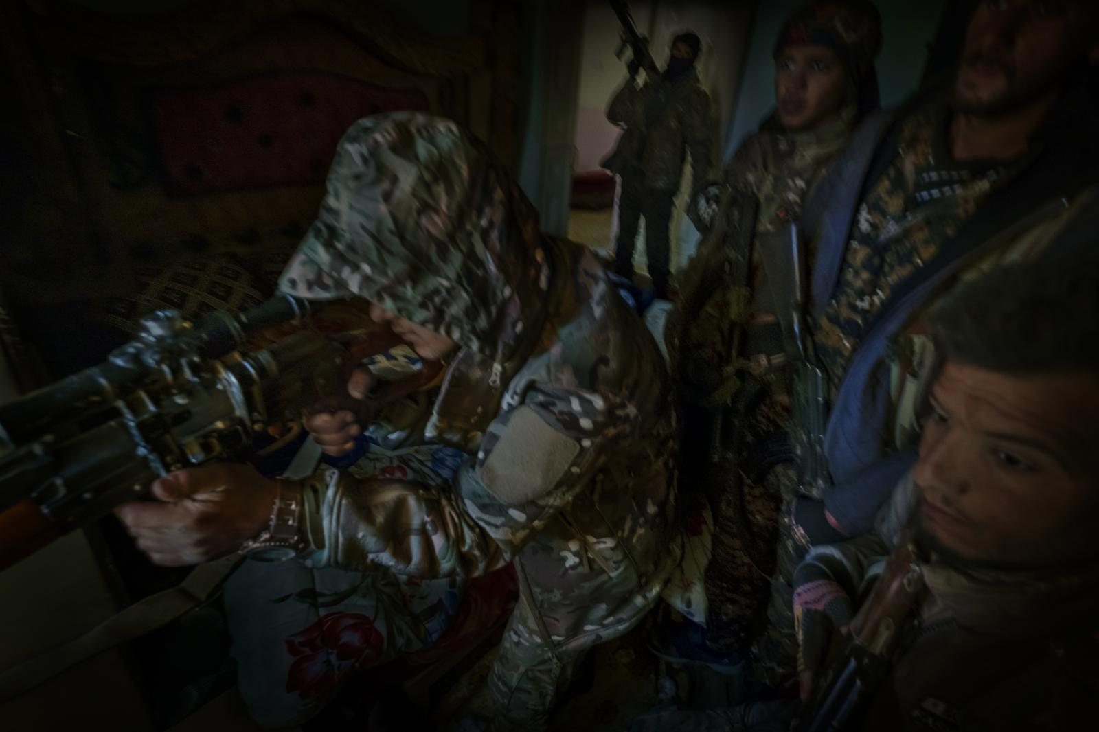 Members of the Syrian Democratic Forces (SDF) with a sniper, in a house situated on the front line in Deir ez-Zor, during the final battle before the fall of the ISIS caliphate (Syria).