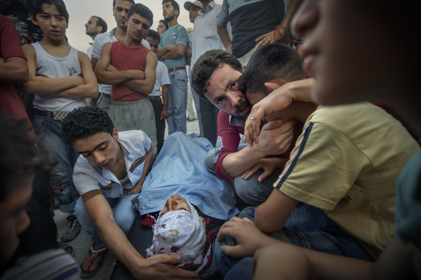 A father comforts his son over the death of his brother, in the besieged martyr city of Aleppo, at the cemetery in Karm Al Jabal (Syria, 2012)