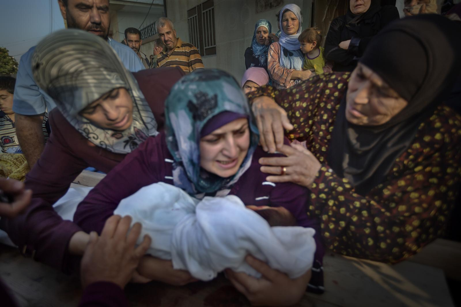 A sniper killed a 5-year-old boy named Yazan Gassan Rezk with a single shot to the head, at an access point to the city of Al Qasir. His mother cries as she clutches her son's corpse before the funeral. That same day, 6 people were killed and 37 wounded by bombings in the city surrounded by forces loyal to Bashar al Assad while helicopters circled overhead. This city was a rebel stronghold in Homs province (Syria, 2012)