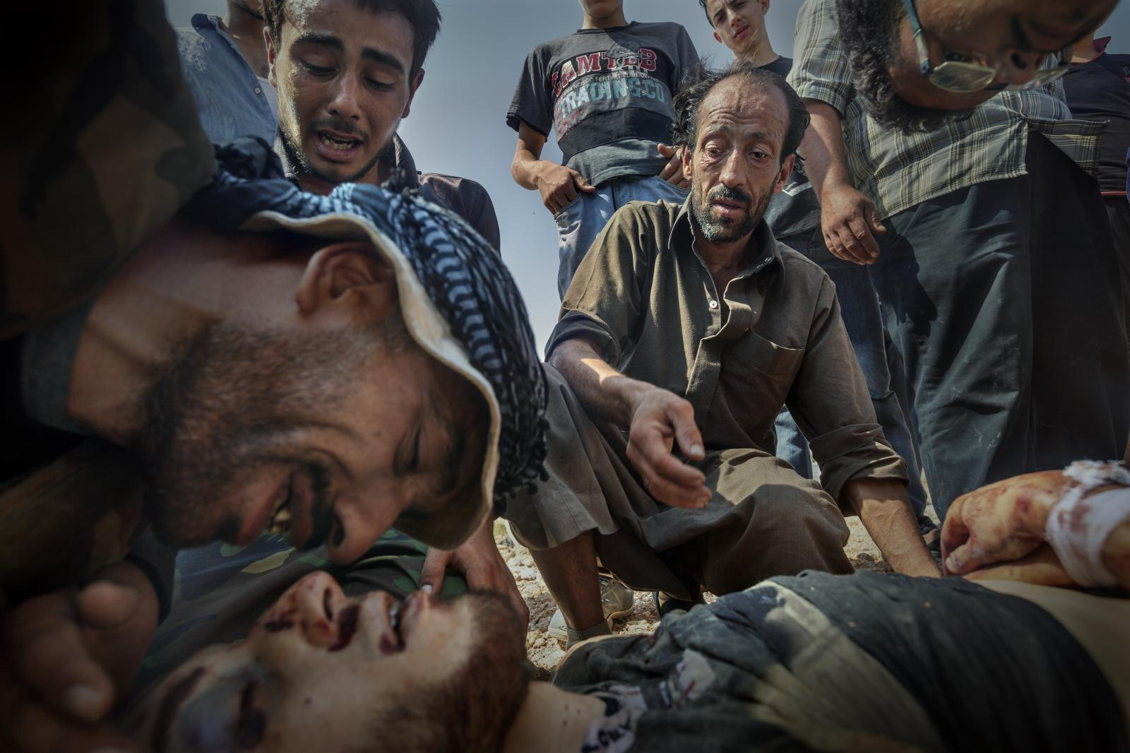 A father cries over his son killed by a government helicopter, at a cemetery on the outskirts of the city. The victim's brother cries with him. He was trying to save a child wounded by a helicopter and the helicopter fired, killing them both. Aleppo (Syria, 2012)